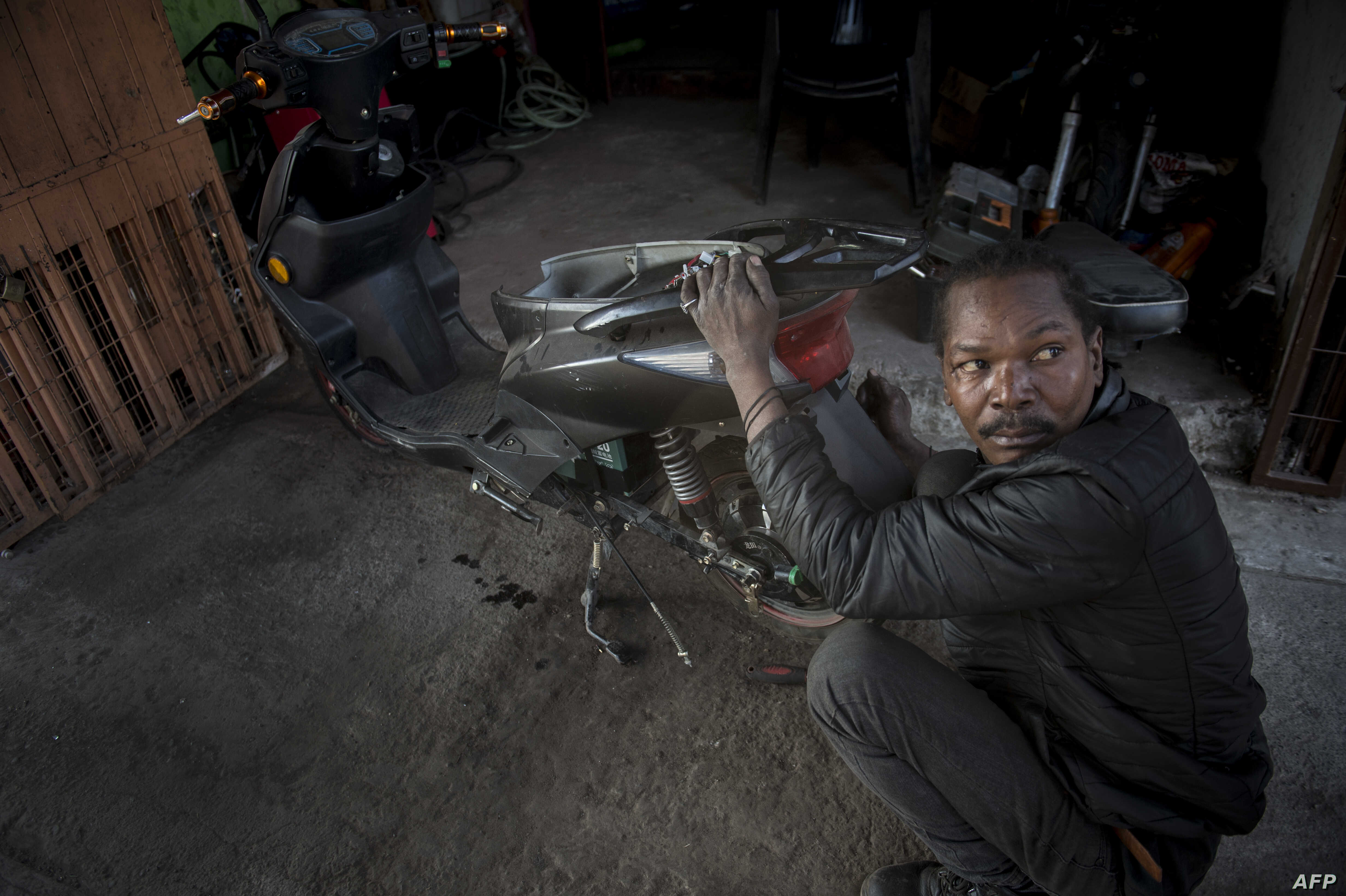 A Haitian mechanic works on a motorcycle at a workshop in the commune of Quilicura in Santiago, on April 26, 2018.