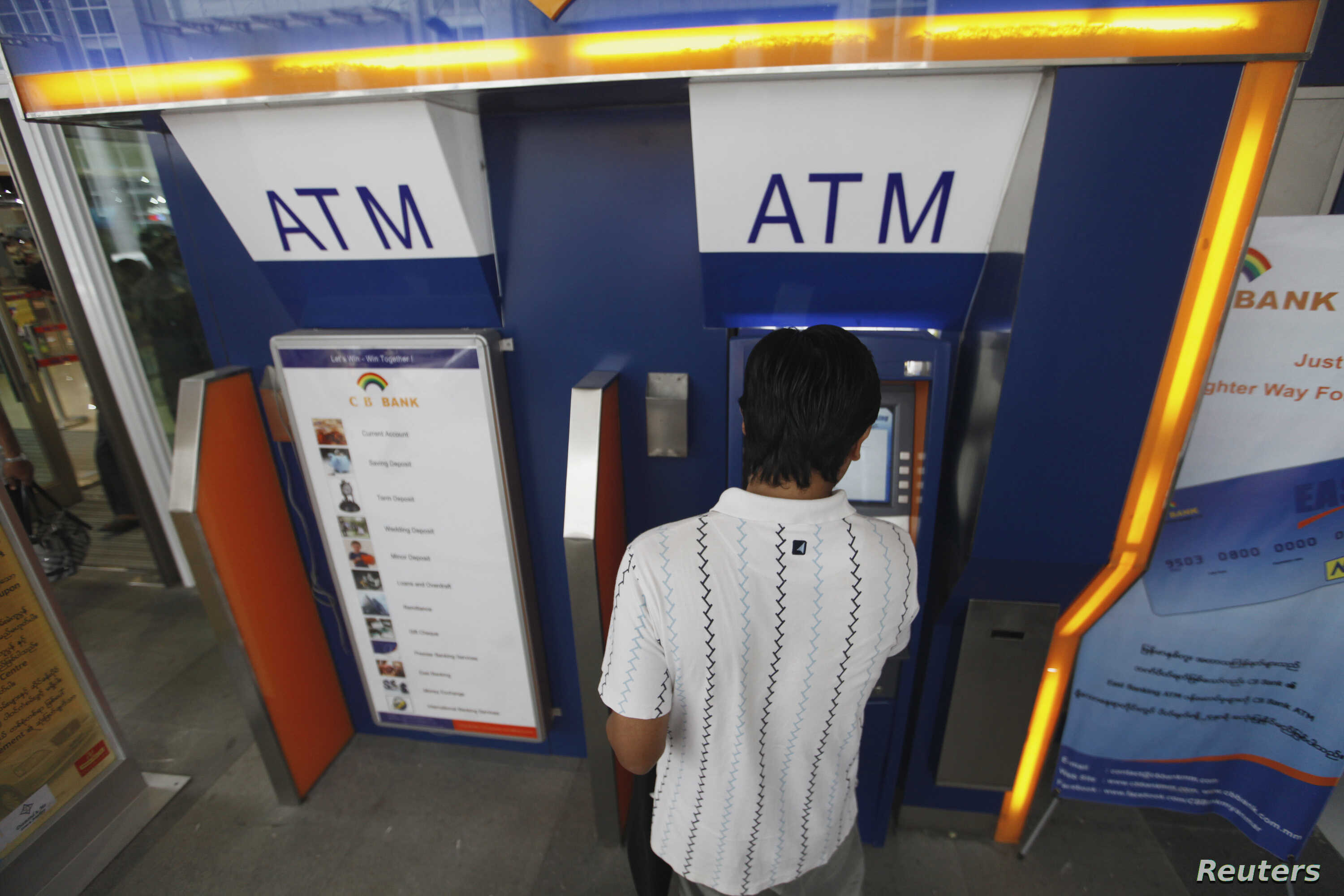 A man uses an automated teller machine (ATM) machine at a shopping center in Yangon, Burma, May 27, 2012.