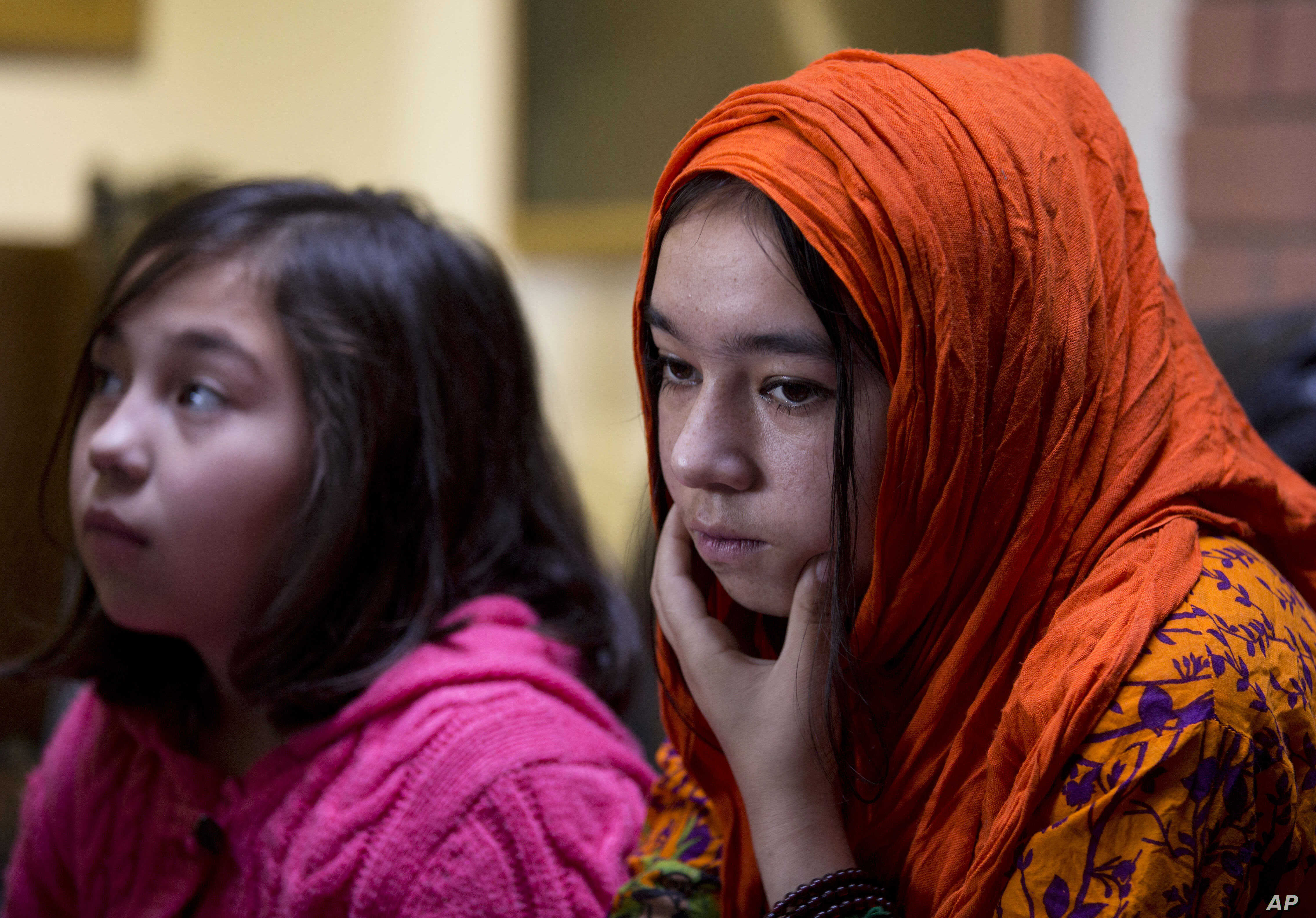In this Nov. 29, 2018 photo, Shahnaz, 16, right, and Shakeela, 12, daughters of Mir Aman, speak to The Associated Press, in Islamabad, Pakistan.