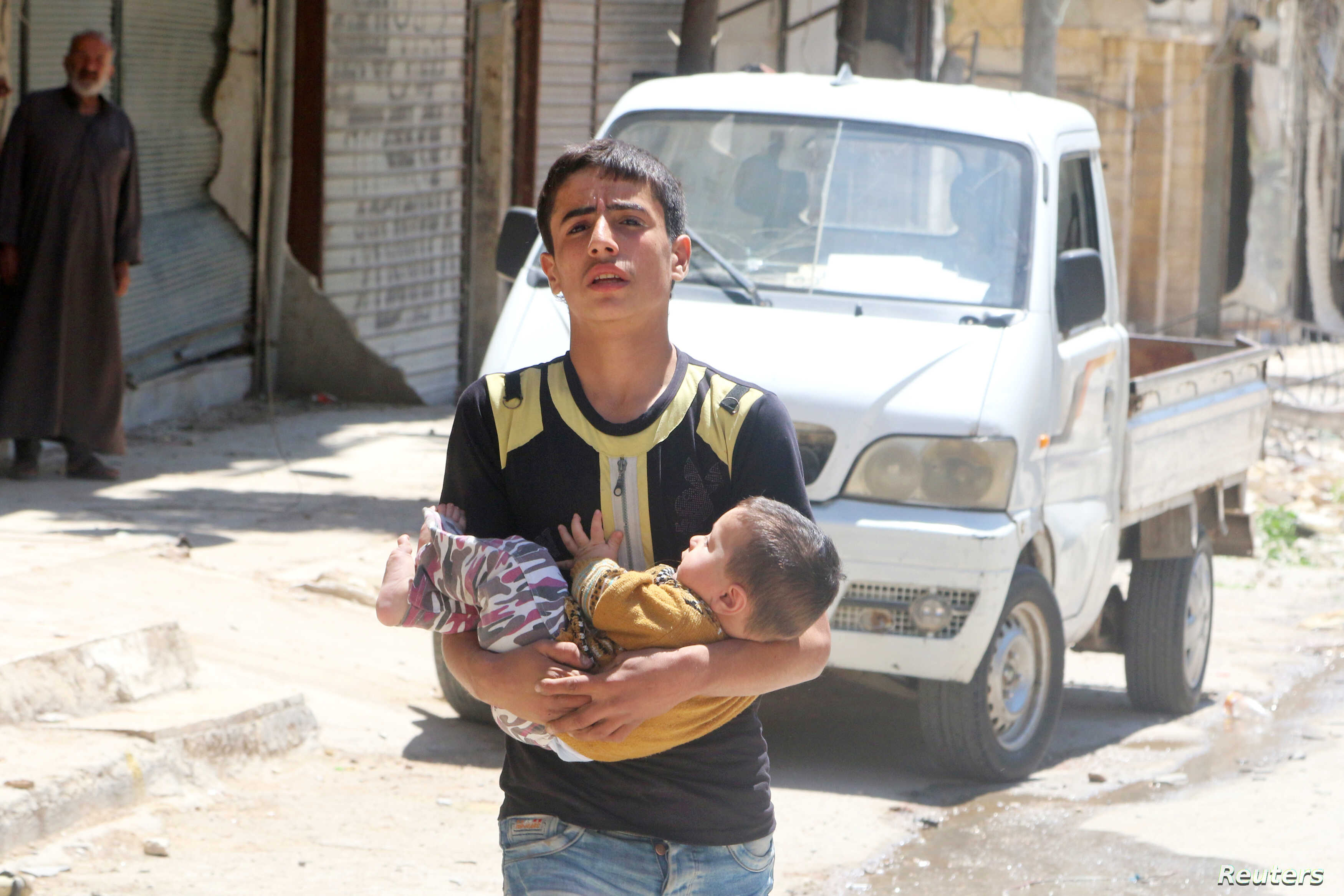 A civilian evacuates a baby from a site hit by airstrikes in the rebel-held area of Aleppo's al-Fardous district, Syria, April 29, 2016.