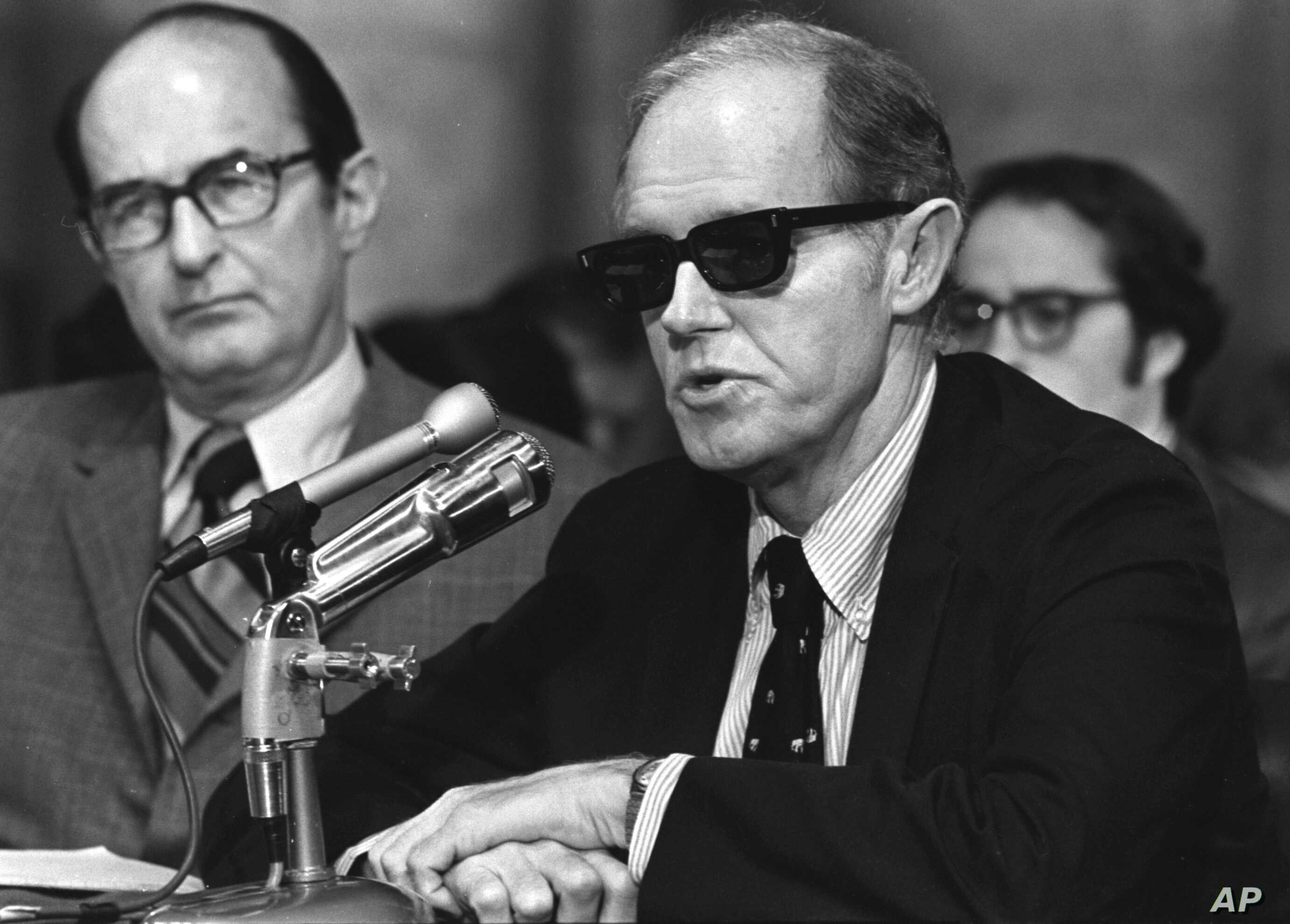 FILE - Convicted Watergate conspiritor E. Howard Hunt, wearing dark glasses, begins his seconds day of testimony before the Senate Watergate Committee in this Sept. 25, 1973 photo in Washington, D.C.  Hunt helped organize the Watergate break-in that ...
