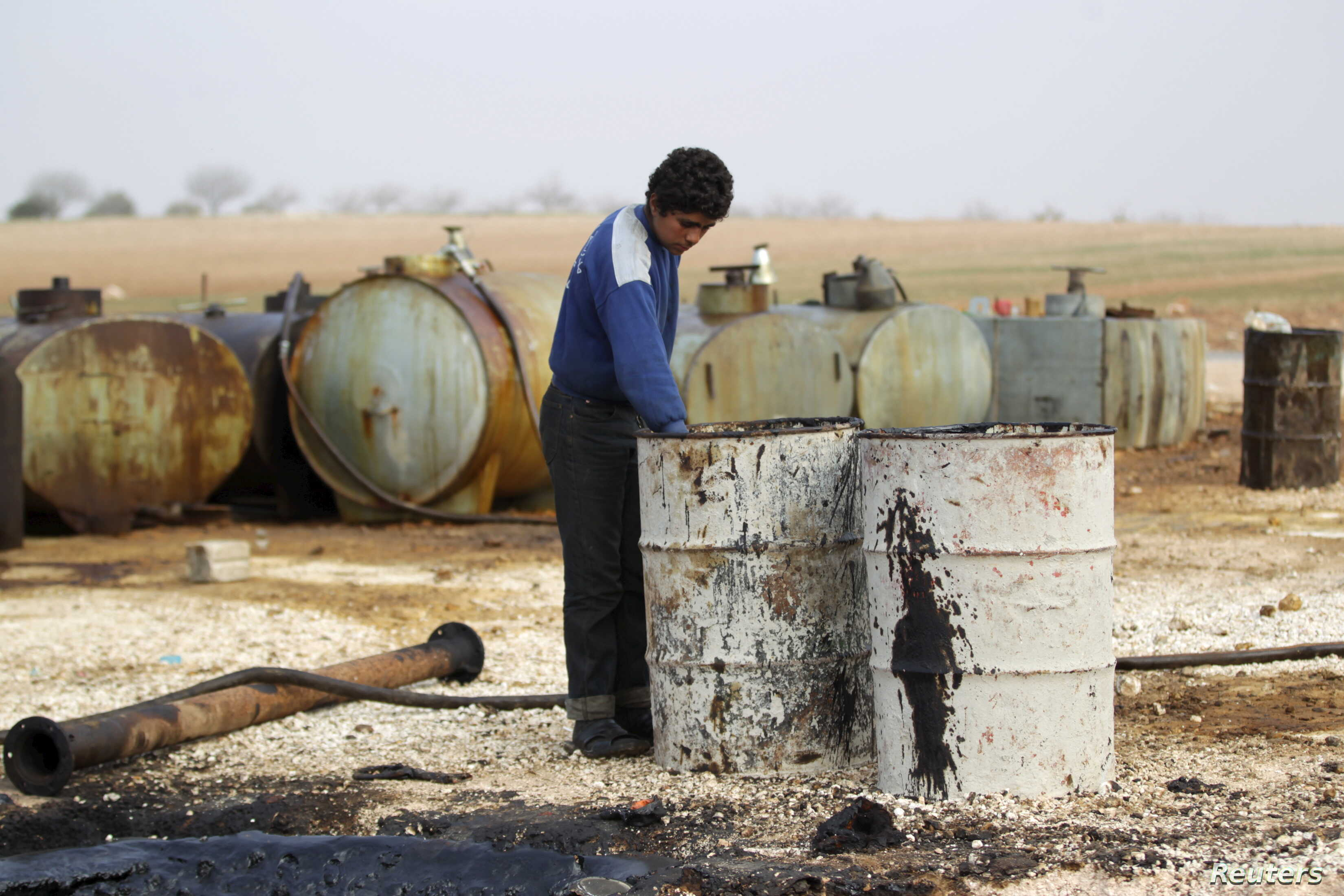 A youth works at a makeshift oil refinery in Syria that, according to its owner, gets the crude oil from Islamic State-controlled areas of Syria and Iraq.