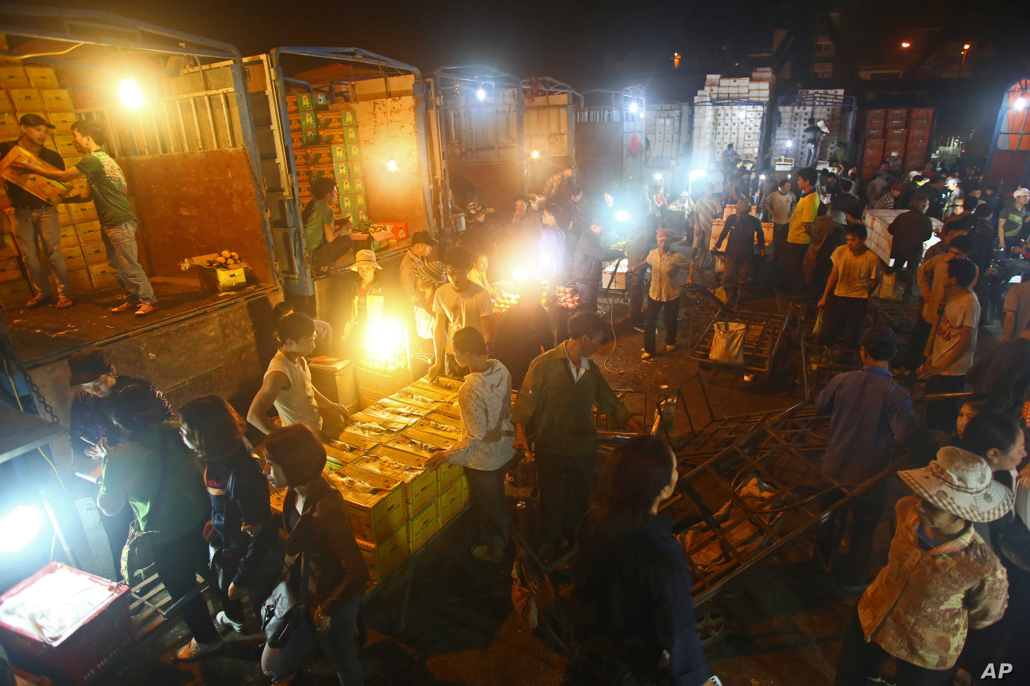 FILE - In this March 9, 2013 photo,  porters unload boxes of Chinese fruits near traders at Long Bien wholesale market for fruits and vegetables in Hanoi, Vietnam.