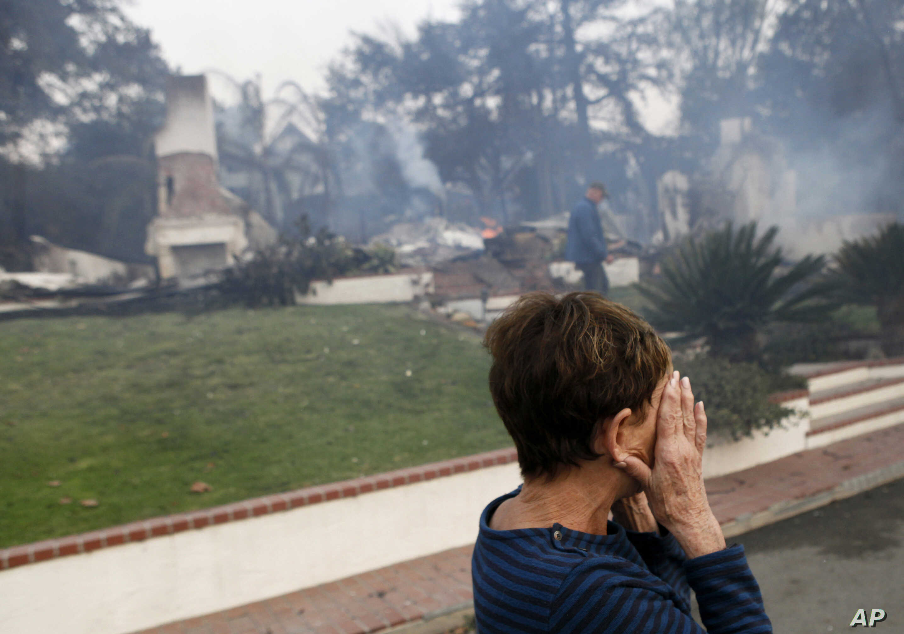 FILE - A woman cries as she covers her face near her destroyed home a wildfire swept through Ventura, California, Dec. 5, 2017.