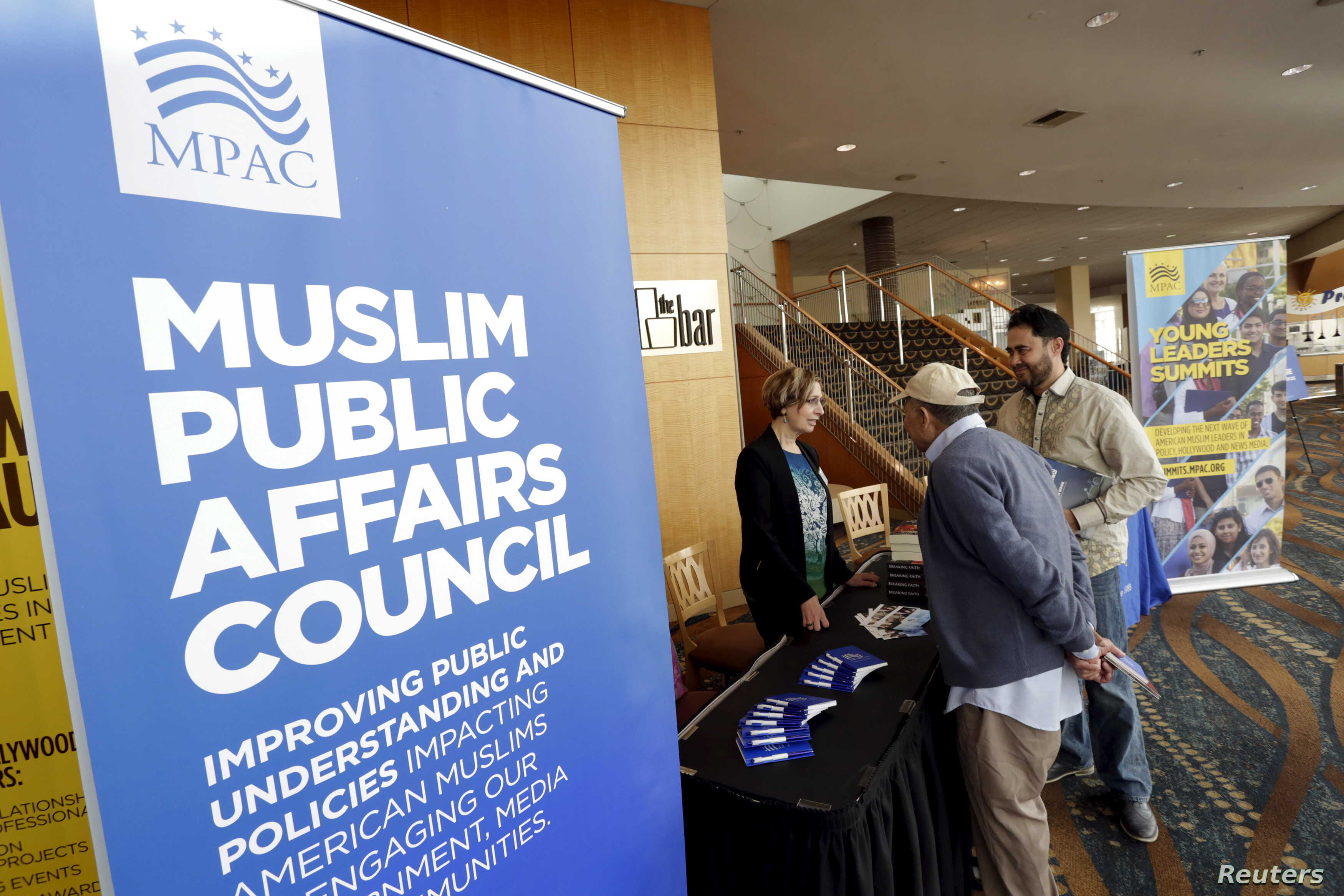FILE - People stand at the registration desk for a Muslim Public Affairs Council convention in Long Beach, Calif., Dec. 5, 2015.