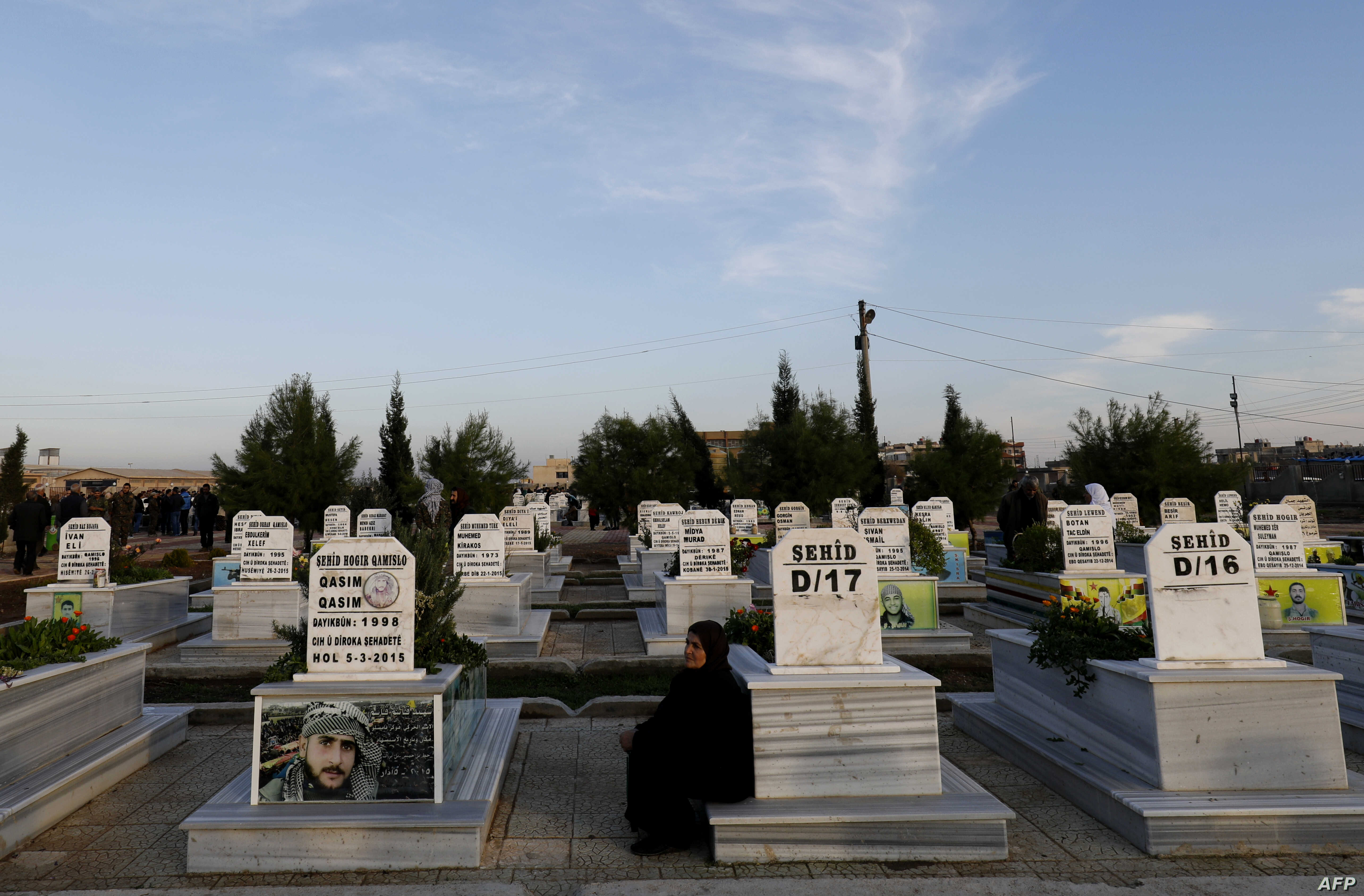 FILE - A woman sits among tombs in a cemetery during the funeral for a Syrian Democratic Forces fighter killed in the town of Hajin during battles against the Islamic State group, in the Kurdish-controlled city of Qamishly in northeastern Syria, on D...