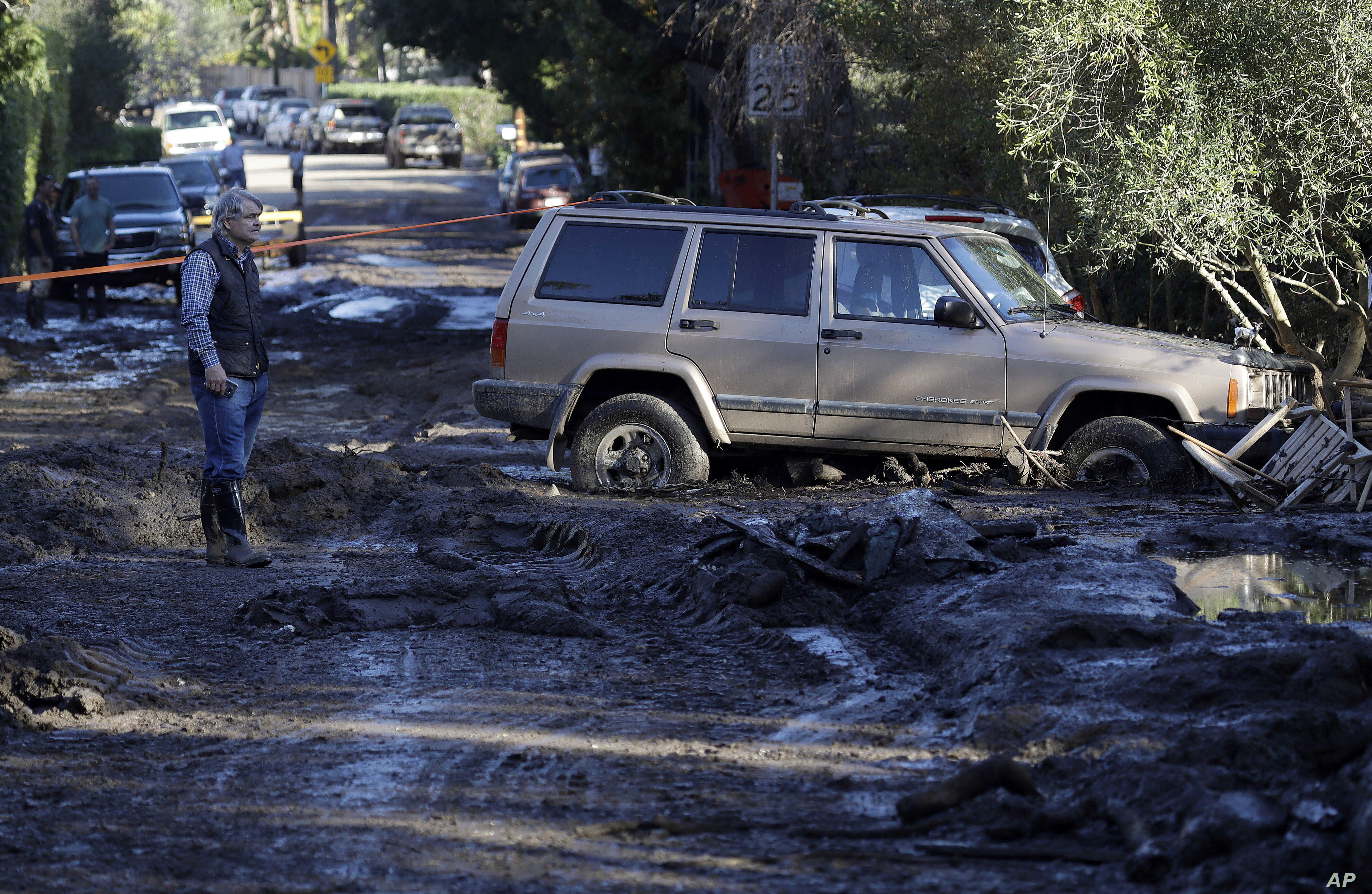 A man stands on a muddy road damaged from storms in Montecito, Calif.,, Jan. 11, 2018. Rescue workers slogged through knee-deep ooze and used long poles to probe for bodies as the search dragged on for victims of the mudslides that slammed this wealt...
