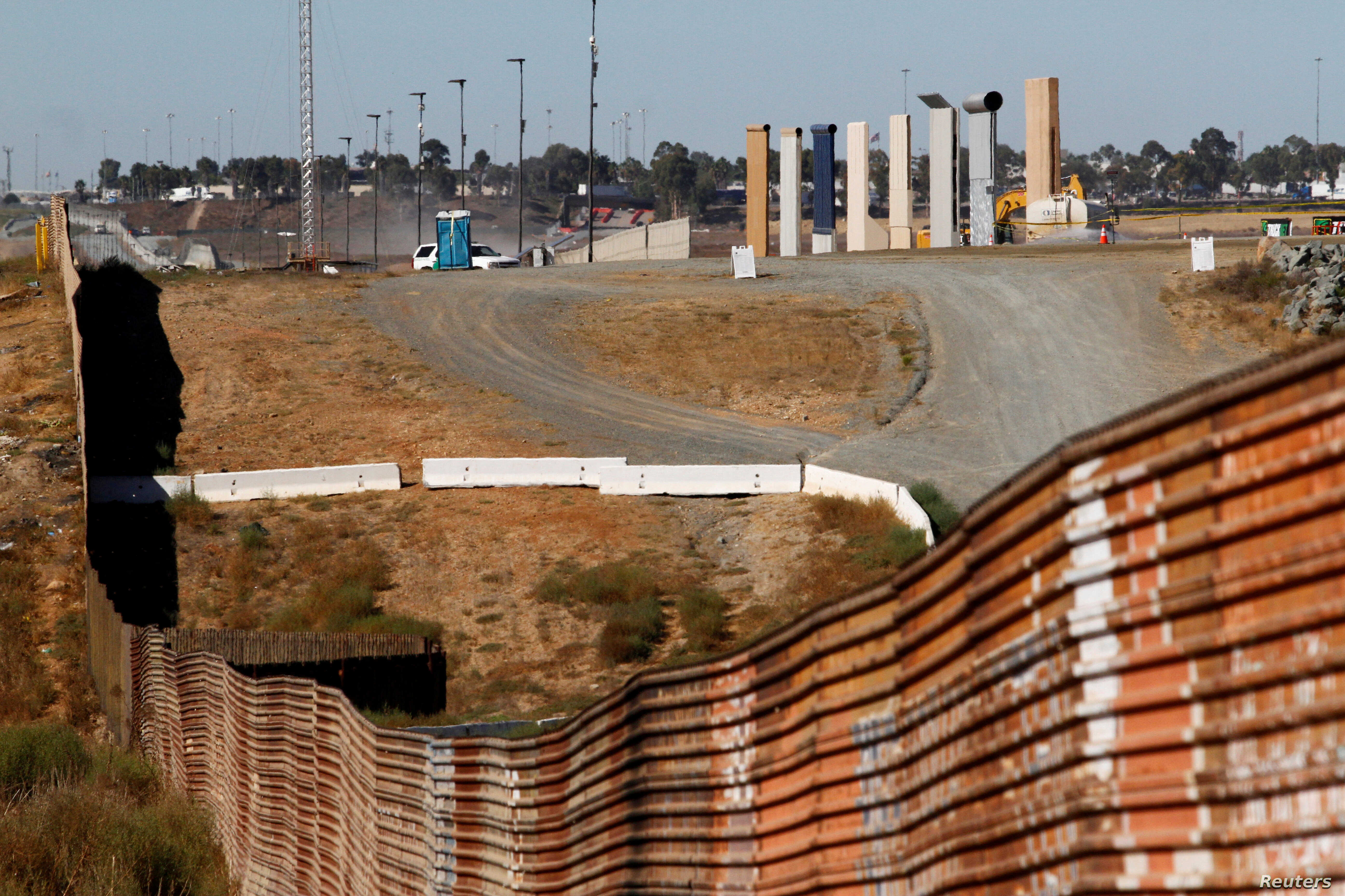 FILE: Prototypes for U.S. President Donald Trump's border wall with Mexico are shown near completion behind the current border fence, in this picture taken from the Mexican side of the border, in Tijuana, Oct. 23, 2017.