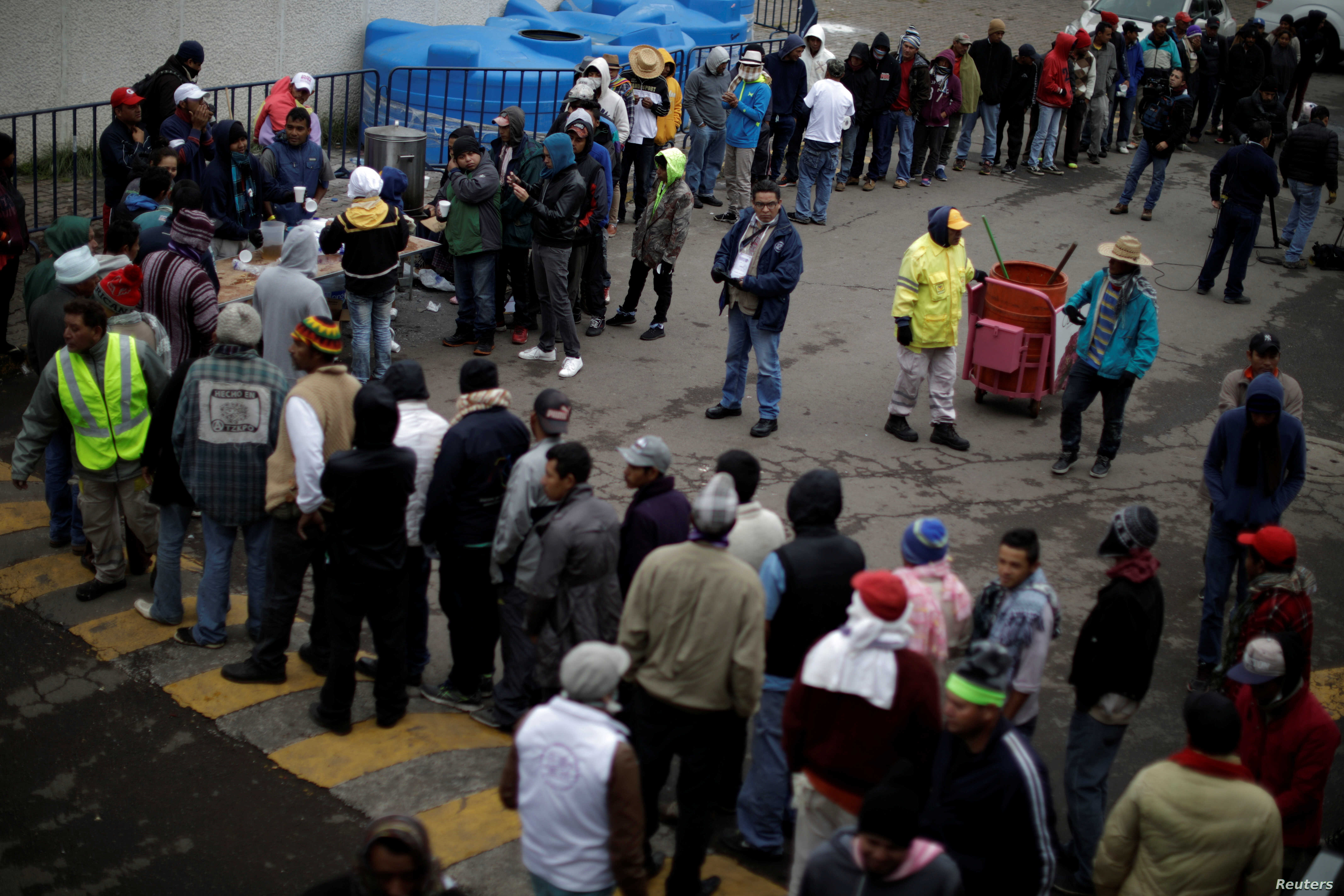 Migrants, part of a caravan of thousands traveling from Central America en route to the United States, line up for food in a makeshift camp in Mexico City, Mexico, Nov. 15, 2018.