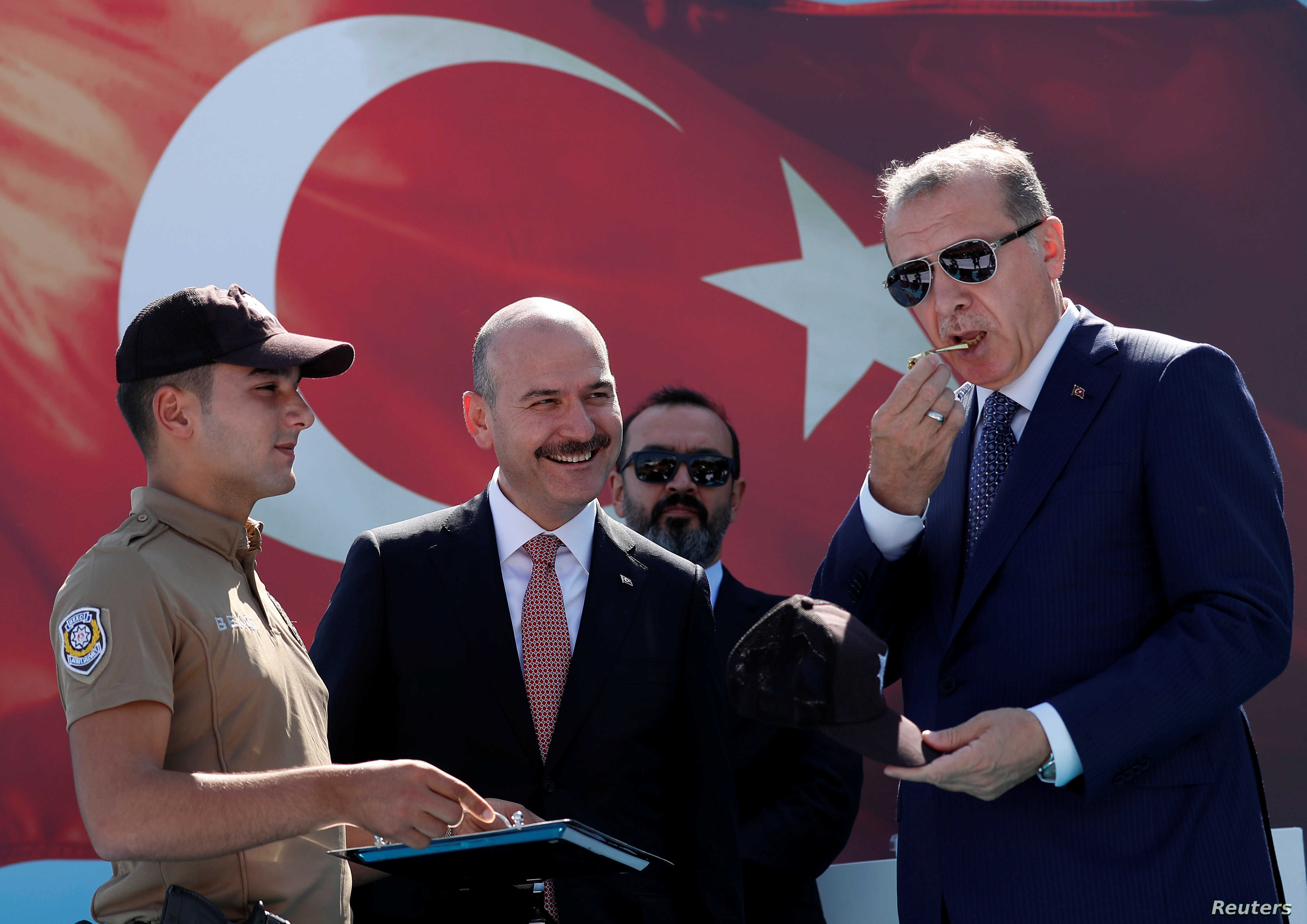Turkish President Tayyip Erdogan, accompanied by Interior Minister Suleyman Soylu, blows a watchmen whistle during a ceremony in Istanbul, Aug. 25, 2017.