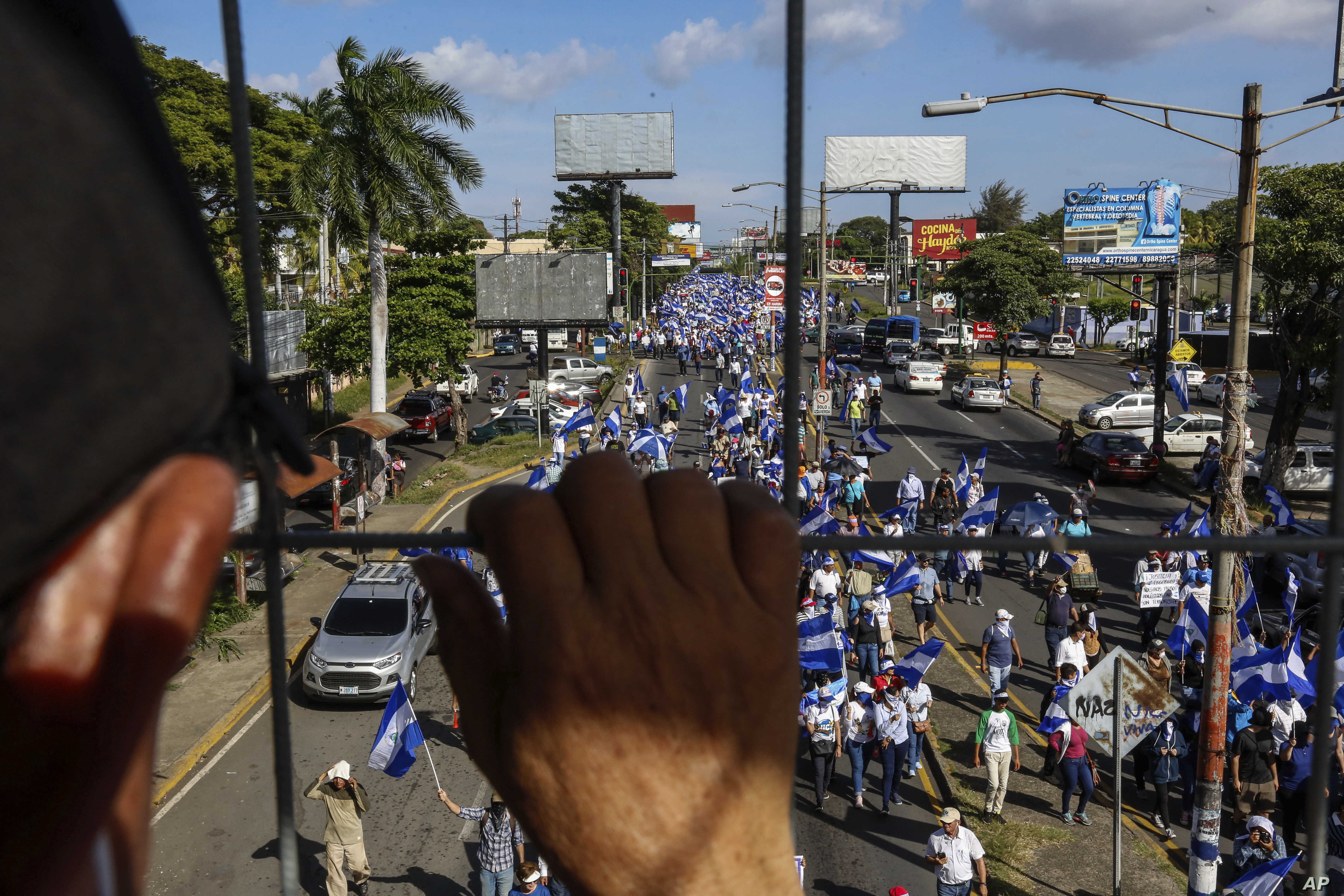 FILE -  An individual watches from above as protestors march below during an anti-government protest in Managua, Nicaragua, Aug. 11, 2018.
