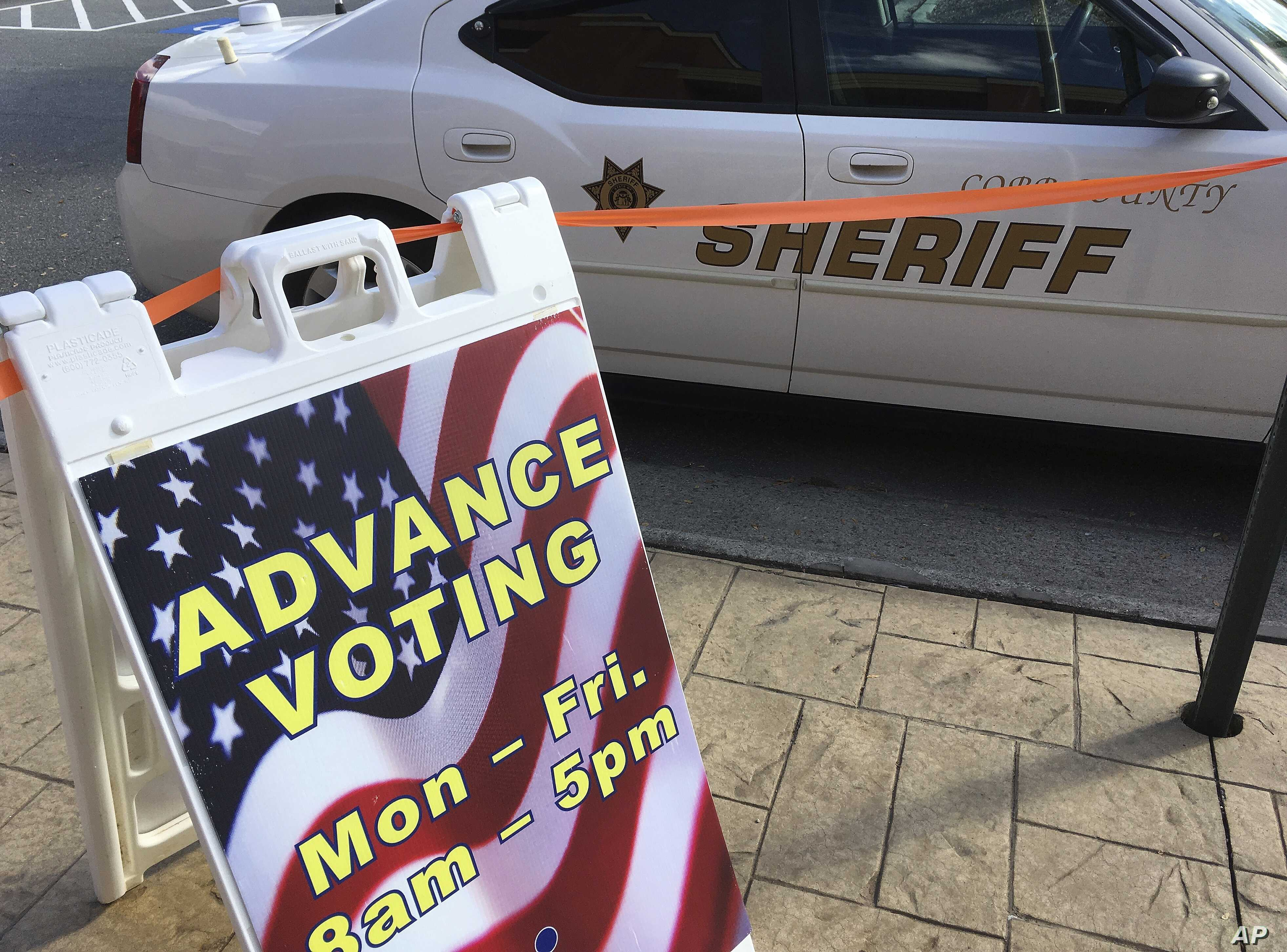 """A sign displays absentee voting hours in Marietta, Ga., as a Cobb County sheriff's deputy sits in his vehicle, Oct. 17, 2016. Facing unprecedented warnings of a """"rigged"""" election from Donald Trump, state officials around the country are rushing to re..."""