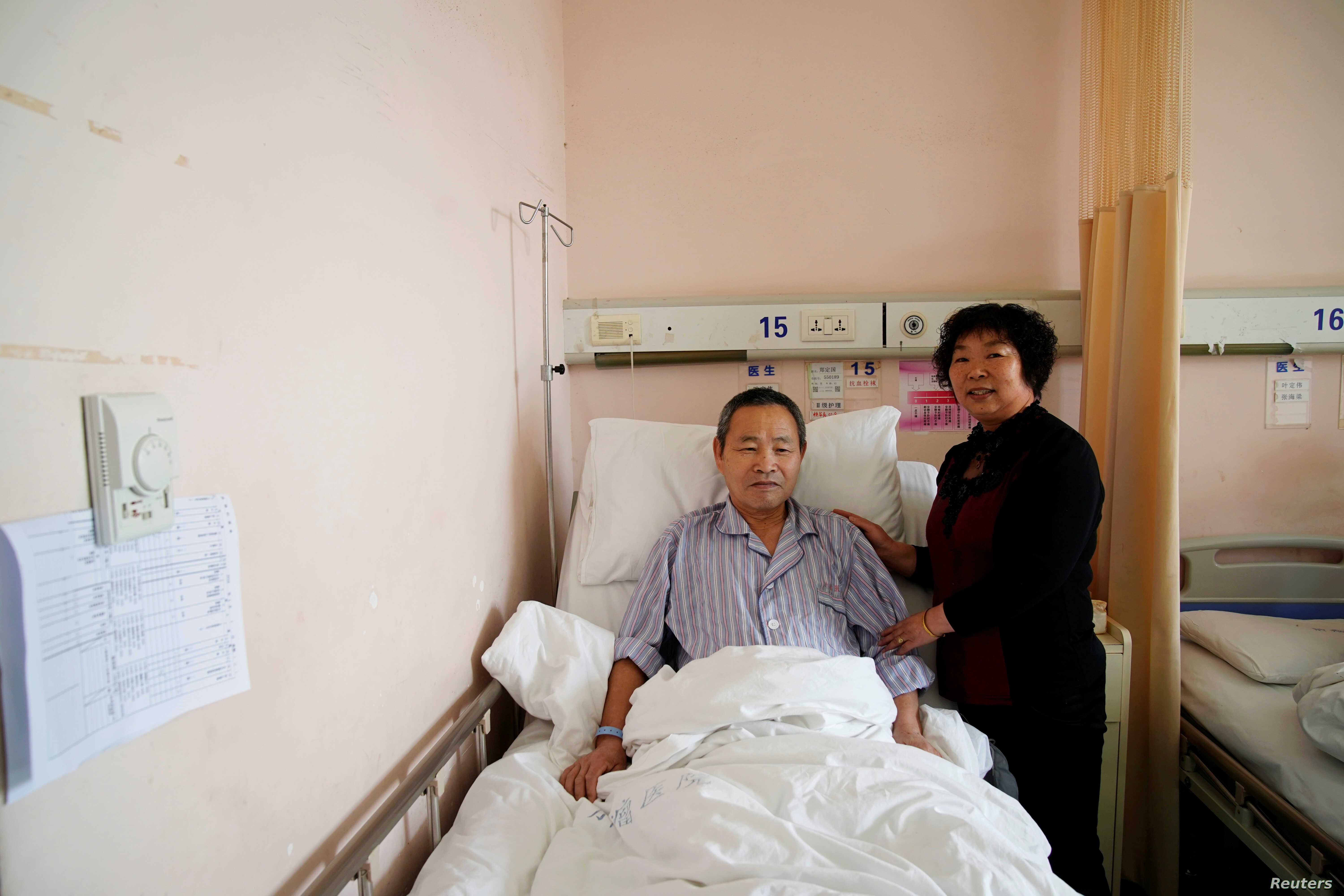 Huang Chenfeng, right, 63, and her husband, Zheng Dingguo, 63, pose for a picture at Fudan University Shanghai Cancer Center in Shanghai, China, Feb. 6, 2018.