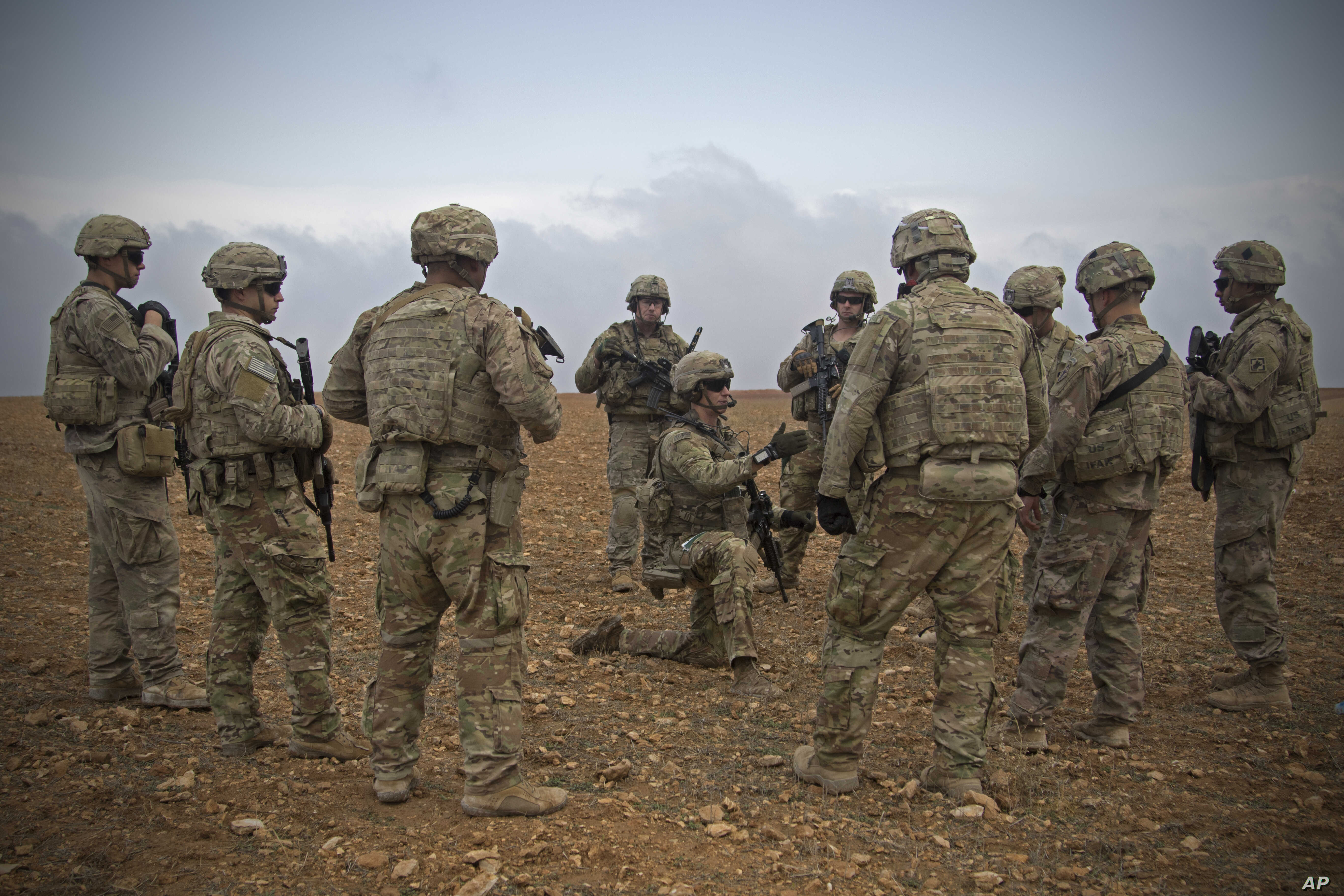 FILE - Photo released by the U.S. Army shows U.S. soldiers gathering for a brief during a combined joint patrol rehearsal in Manbij, Syria, Nov. 7, 2018.