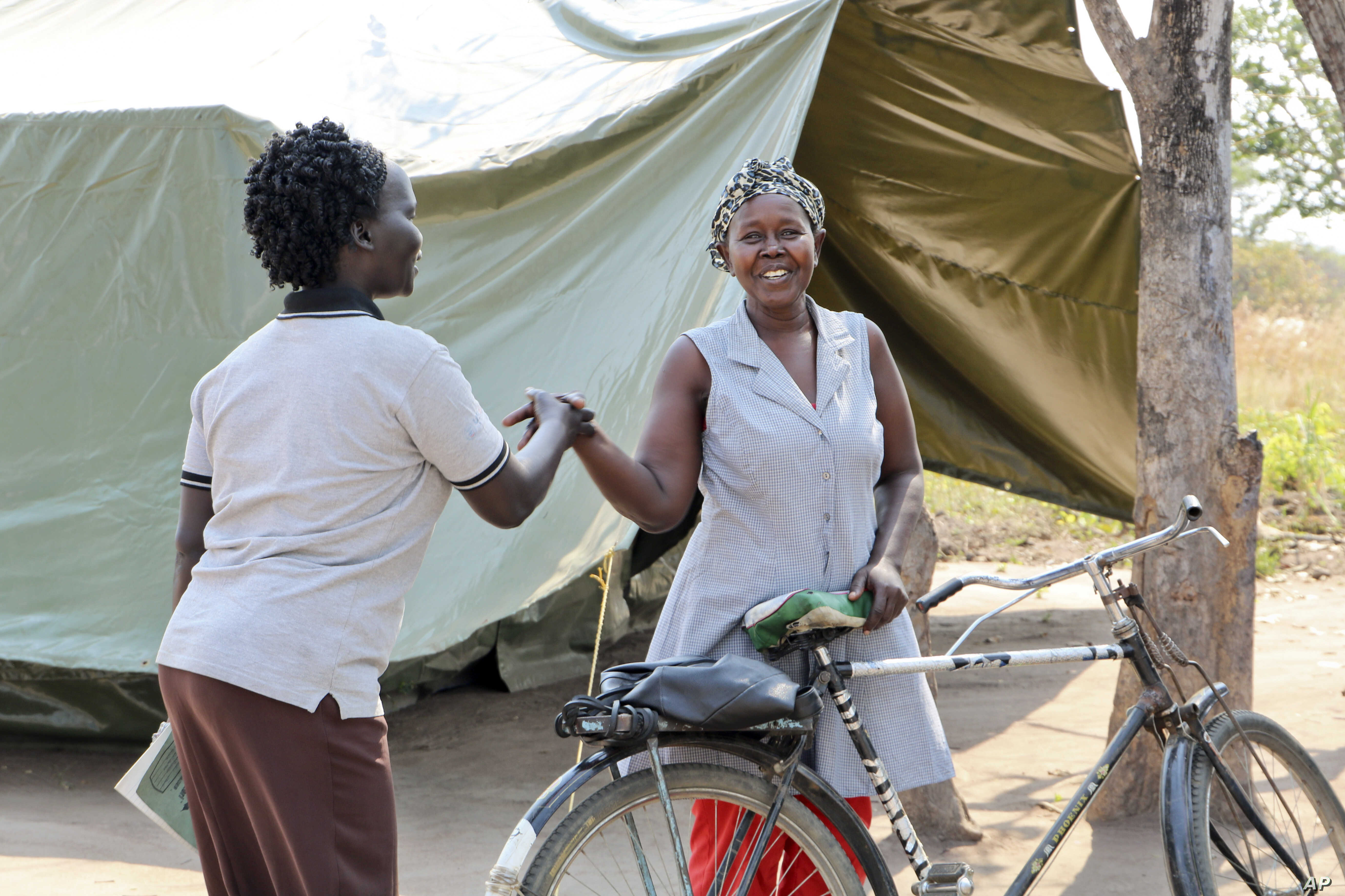 FILE - In this photo taken Jan. 7, 2019, residents greet each other in the Korijo displaced persons camp in the opposition-held part of Kajo Keji county, along the Ugandan border, where a very few people have started to return, in South Sudan. Since ...