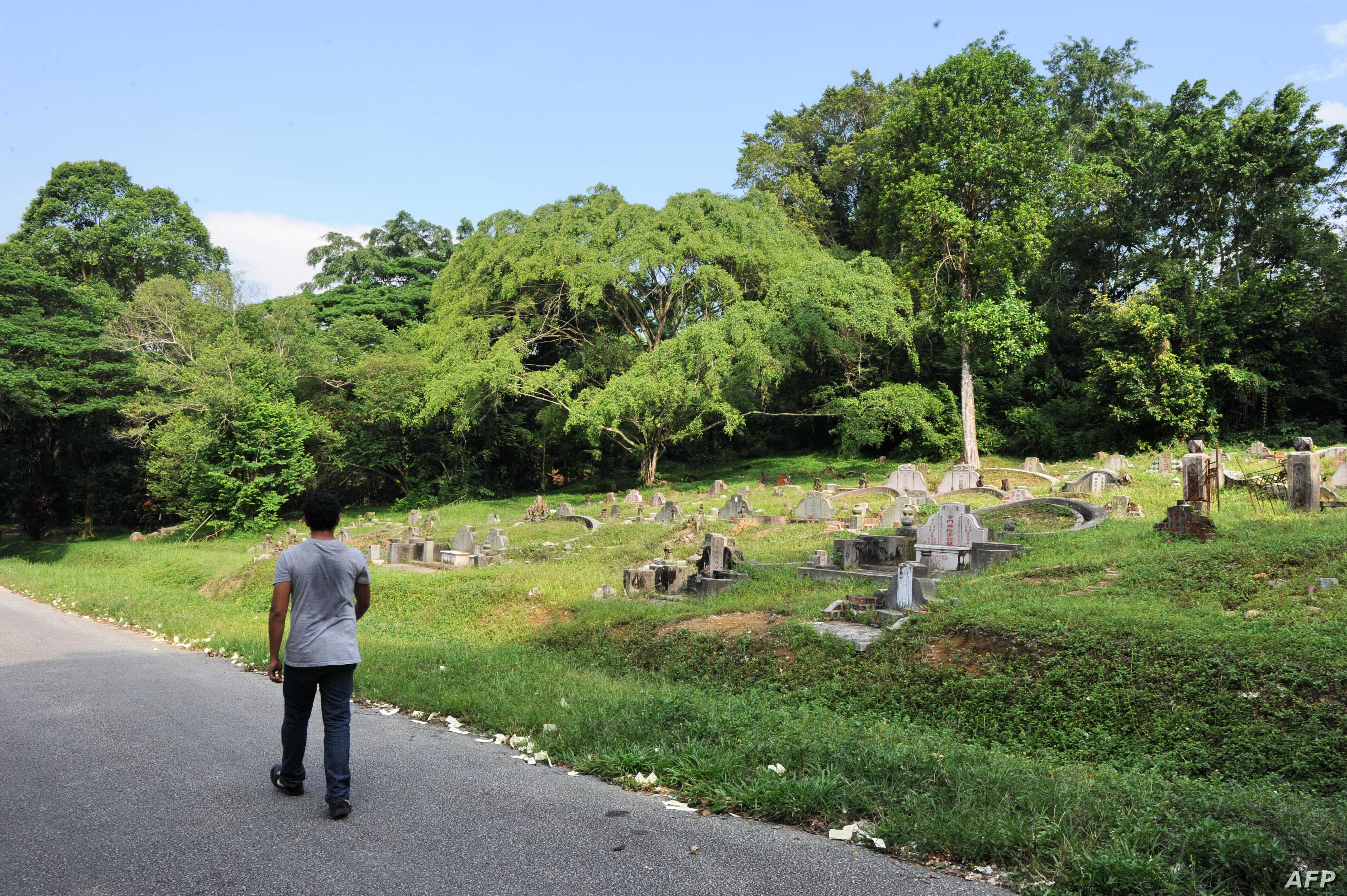 FILE - A man walks past a graveyard at Bukit Brown, one of Singapore's oldest cemeteries, Aug. 16, 2011.