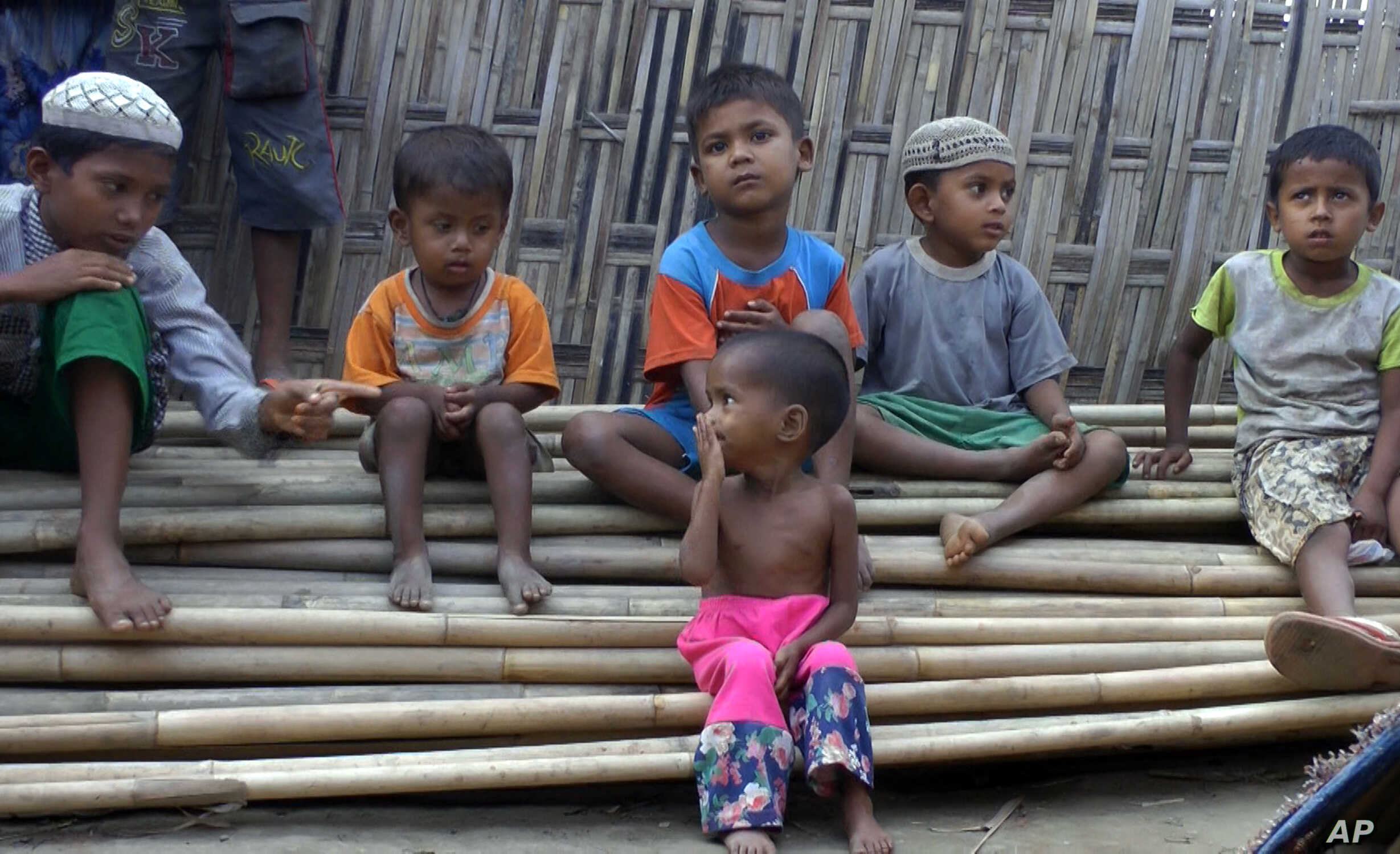 In this March 17, 2017, image made from video, Rosmaida Bibi, center foreground, suffering from severe malnutrition, sits on a pile of bamboo trees with other children at the Dar Paing camp, north of Sittwe, Rakhine state, Myanmar.
