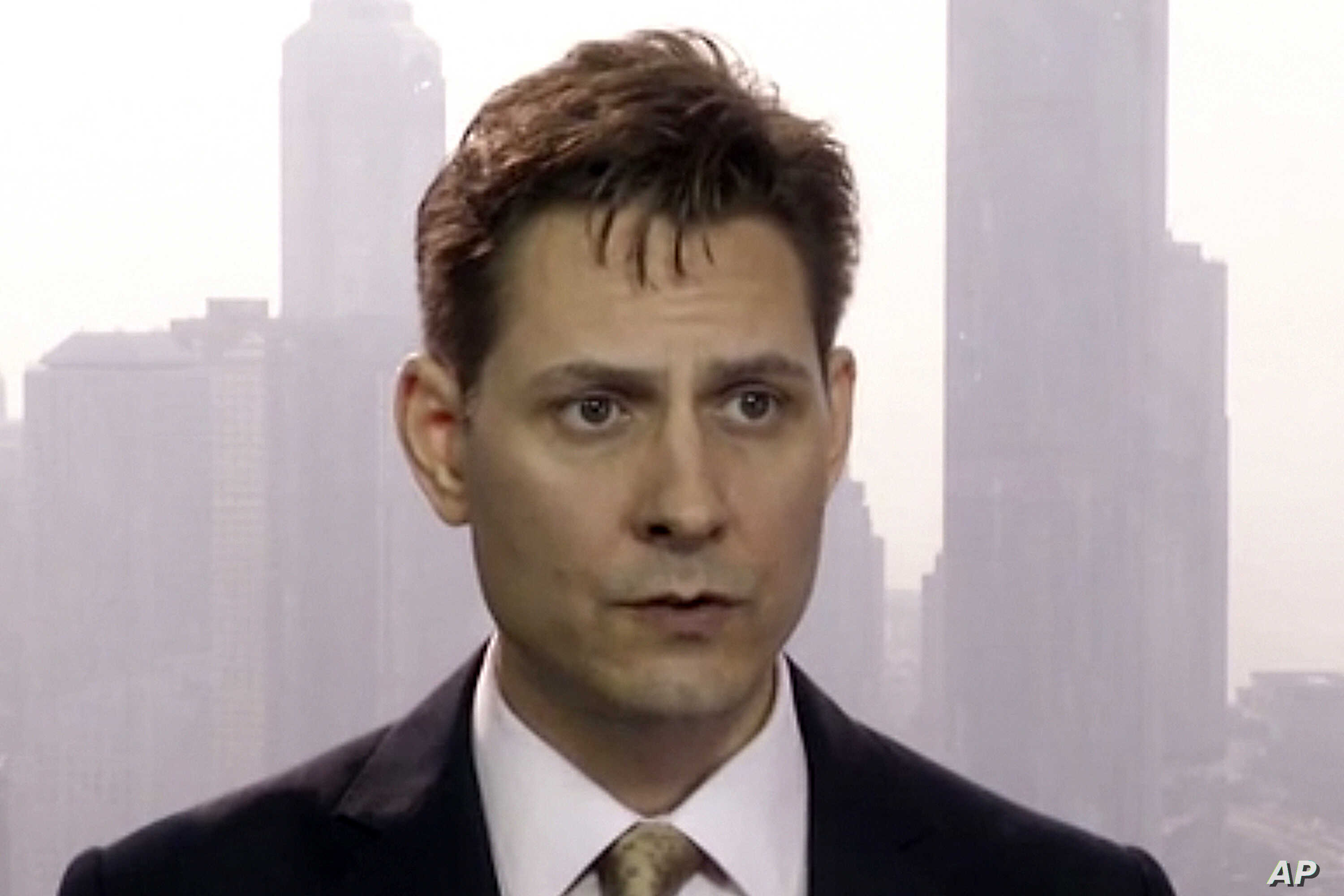 FILE -Image made from a video on March 28, 2018 shows Michael Kovrig, an adviser with the International Crisis Group, a Brussels-based non-governmental organization, speaking during an interview in Hong Kong.