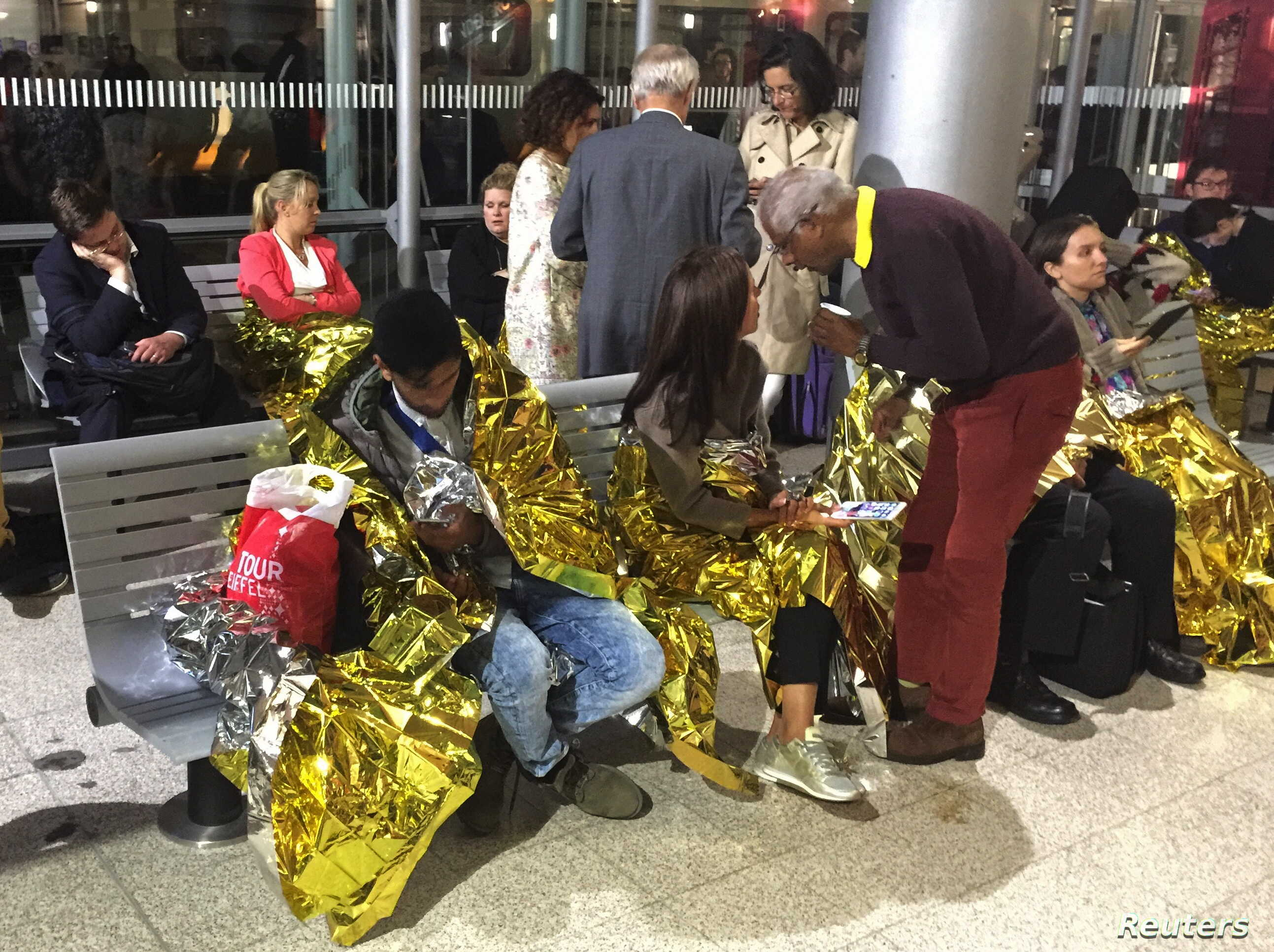 Passengers wrapped in thermal foil blankets given out by emergency services after their Eurostar train was stranded at Calais Station, after intruders were seen near the Eurotunnel, in Calais, France Sept. 2, 2015.