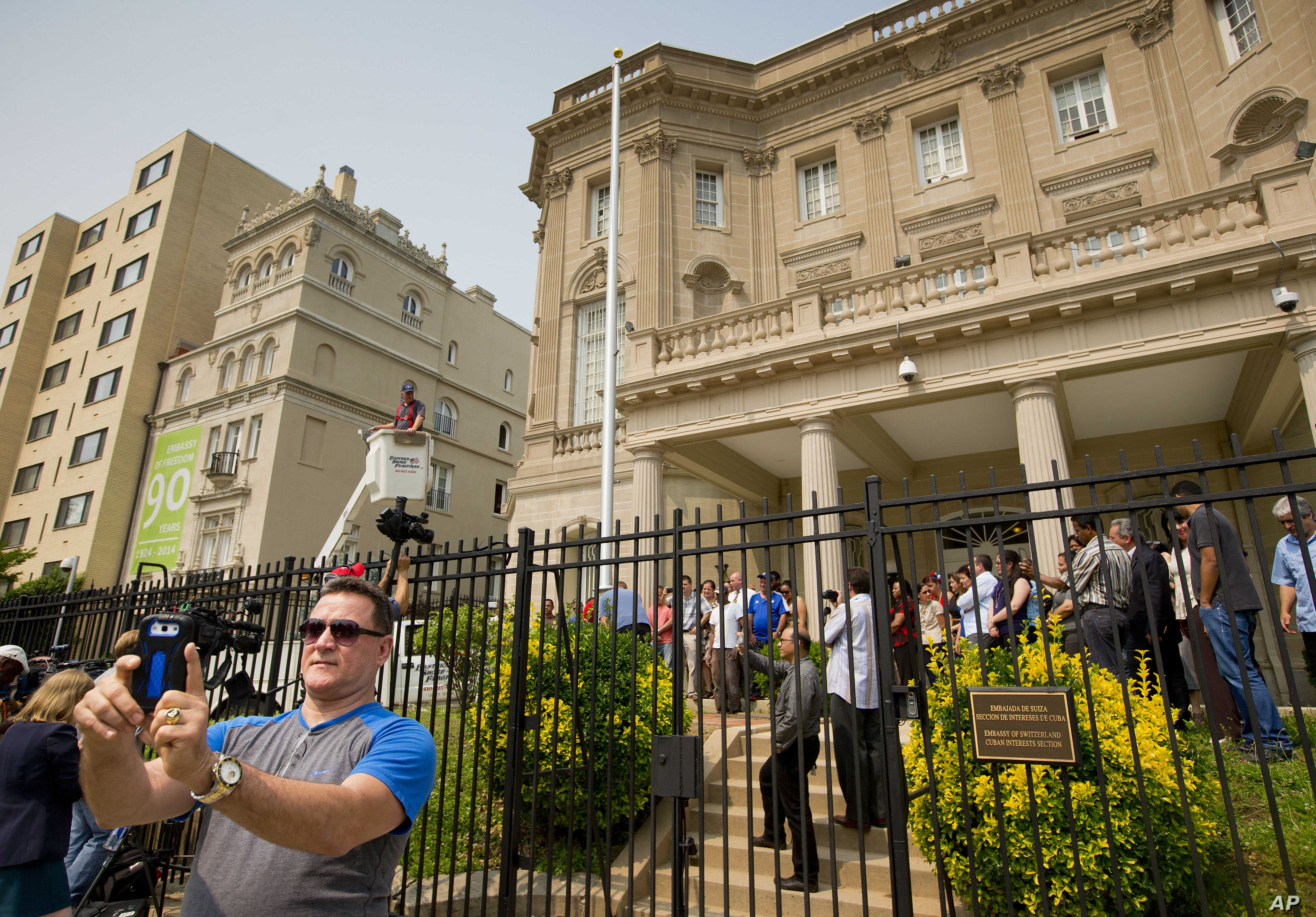 Fernando Rodriguez, left, uses his cellphone to take a selfie as workers from Eastern Shores Flagpoles raise a flagpole at the Cuban Interest Section in Washington in preparation for re-opening of embassies in Havana and Washington, June 10, 2015.