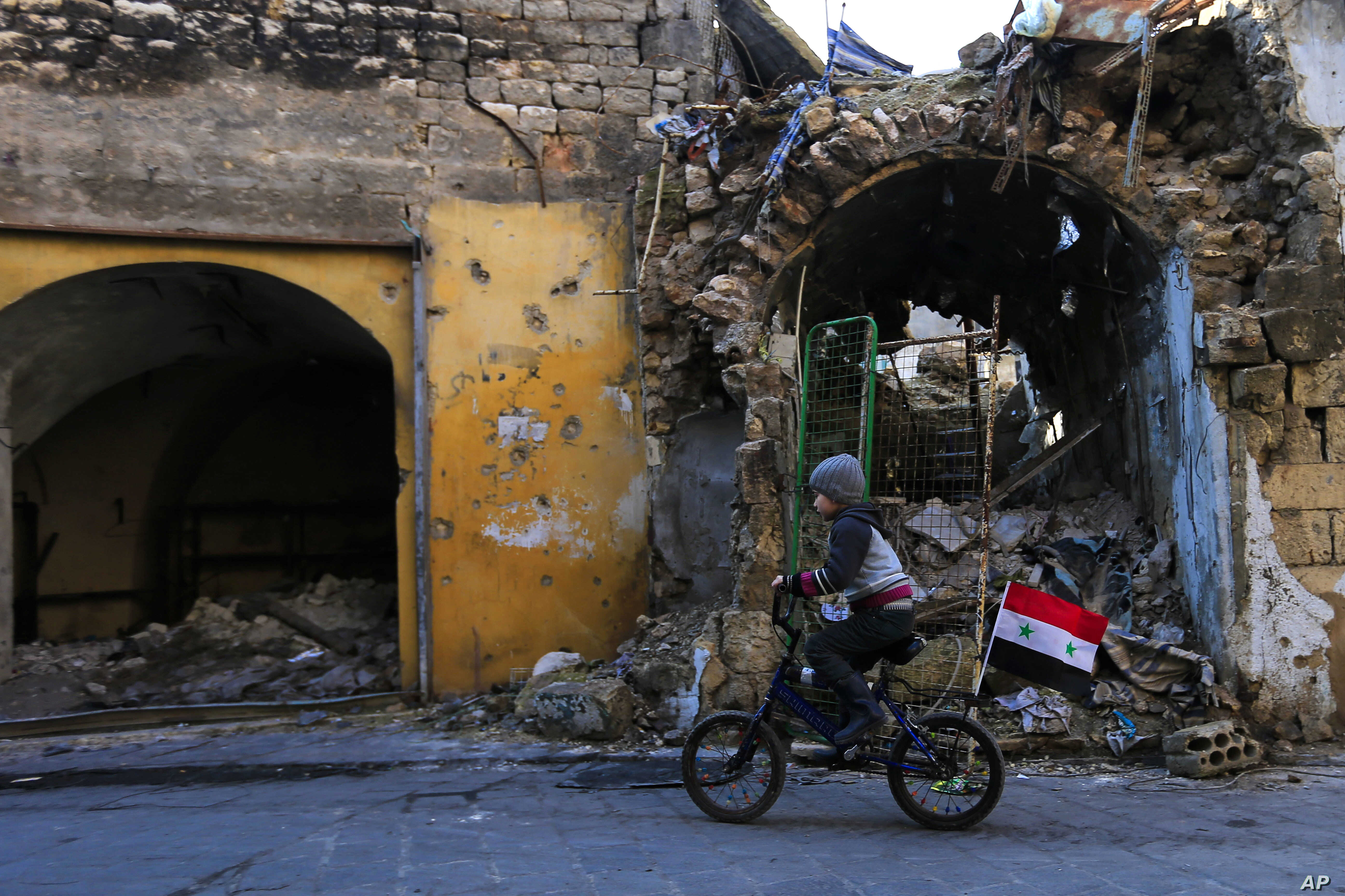 FILE - Syrian boy rides his bike past the destruction in the once rebel-held Jalloum neighborhood of eastern Aleppo, Syria.