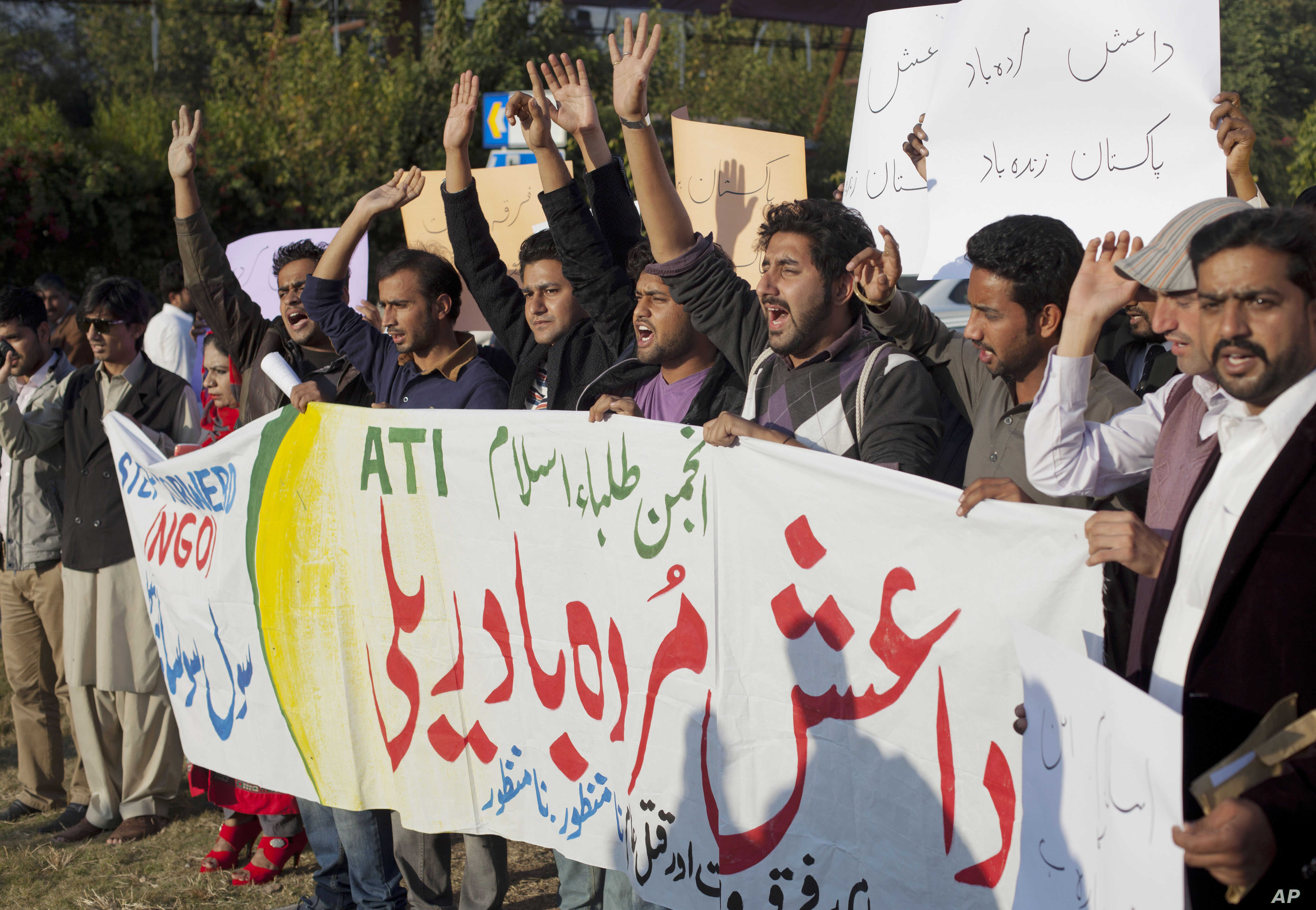 """Pakistani students shout slogans against the Islamic State group holding a banner that reads """"down with Islamic State rally,"""" in Islamabad, Nov 20, 2014."""