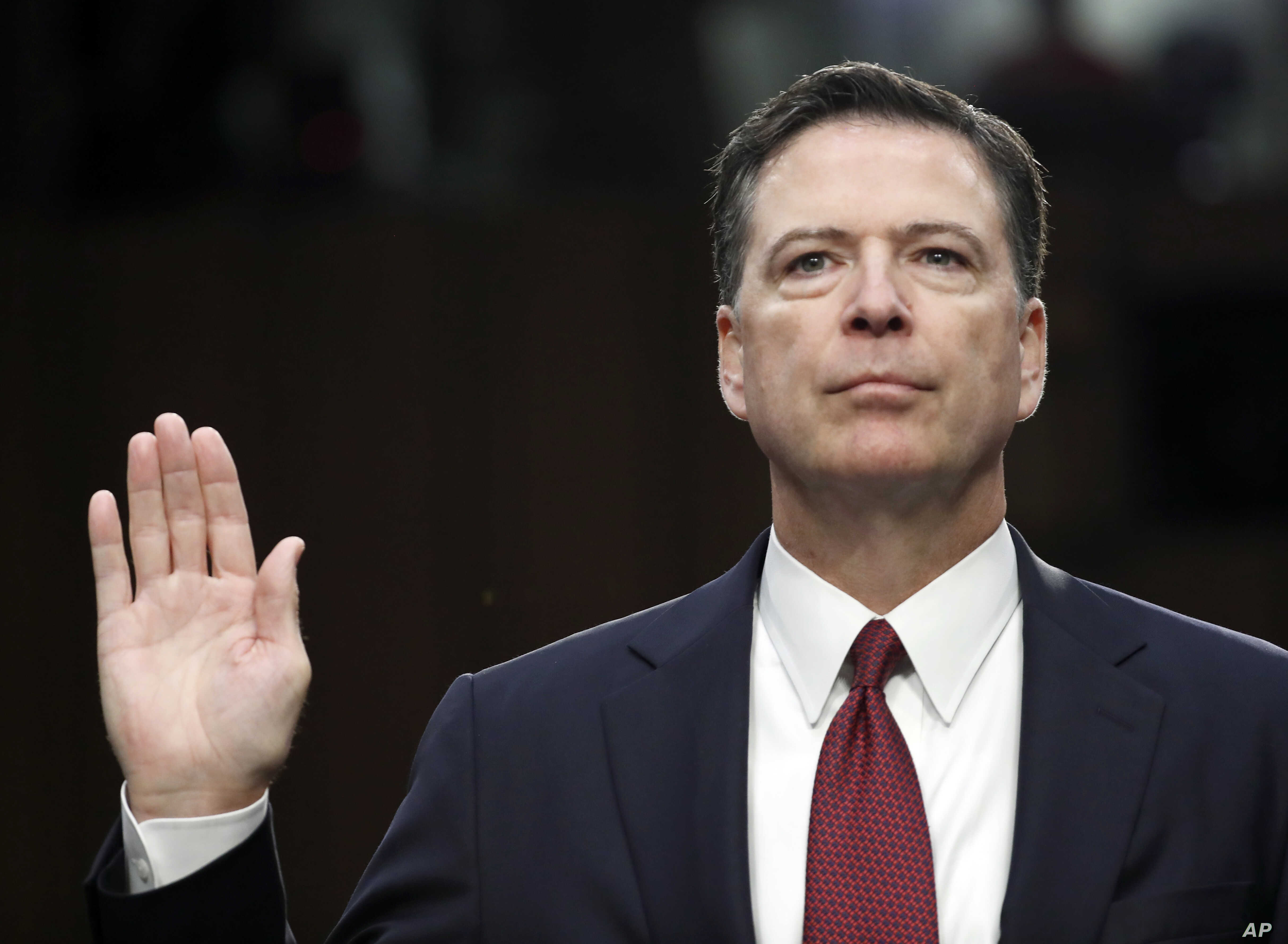 "FILE - Former FBI Director James Comey is sworn in during a Senate Intelligence Committee hearing on Capitol Hill in Washington, June 8, 2017. His publisher is moving up the release date of his memoir ""A Higher Loyalty,"" to April 17."