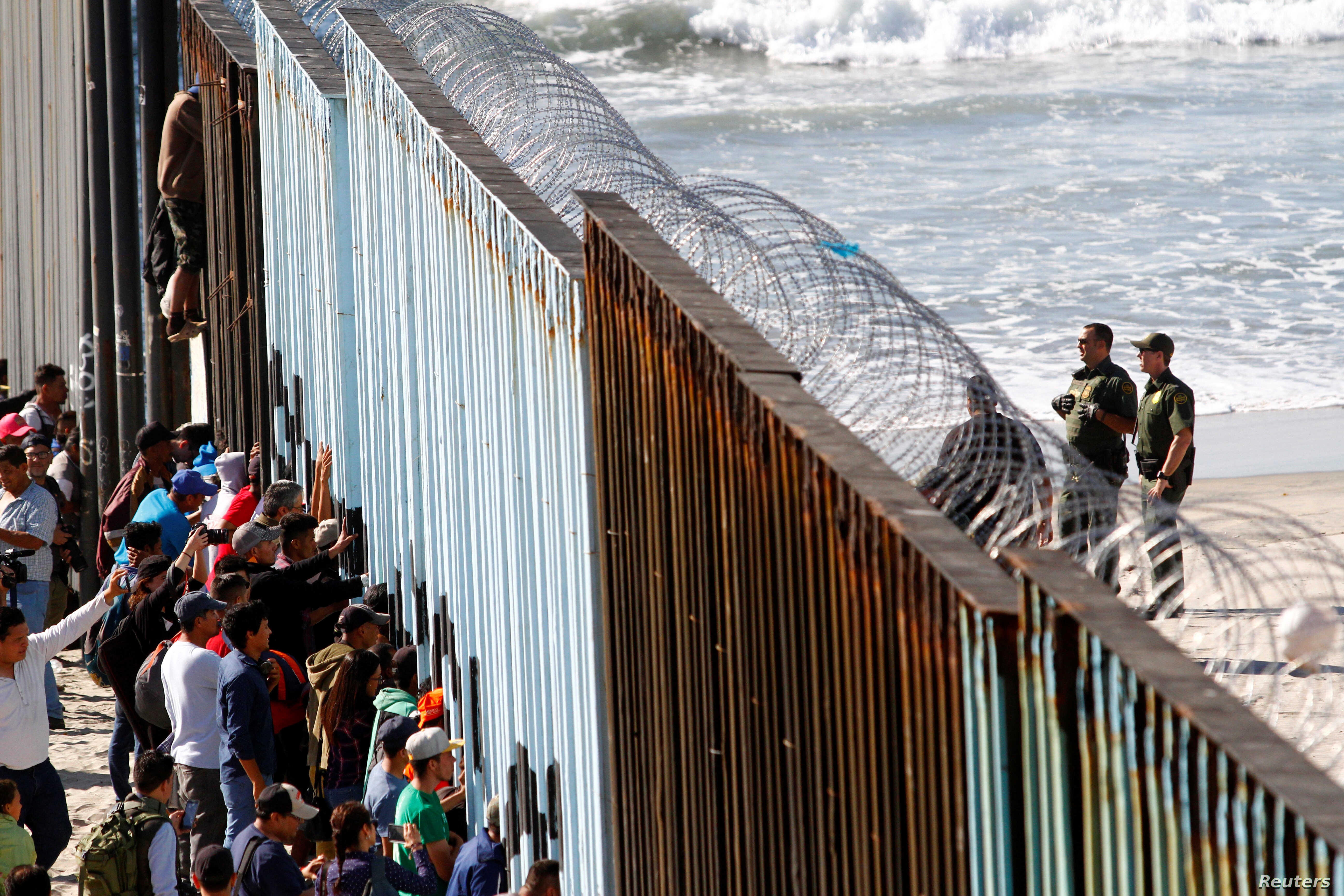 Migrants, part of a caravan of thousands trying to reach the U.S., look through the border fence between Mexico and the United States, in Tijuana, Mexico, Nov. 14, 2018.