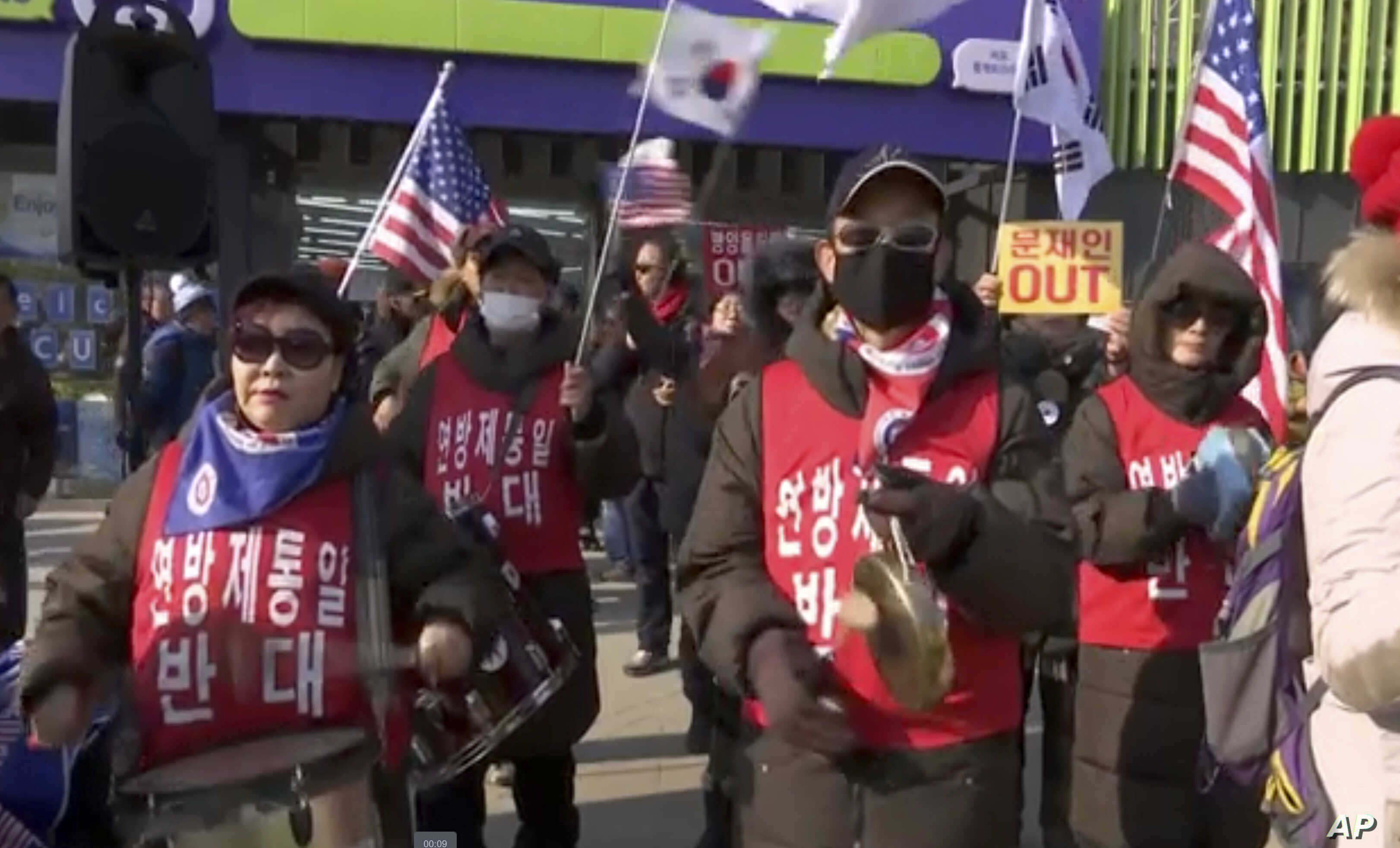 In this grab taken from TV, protesters hold flags and play instruments outside the Olympic Stadium in Pyeongchang, South Korea, Feb. 9, 2018.