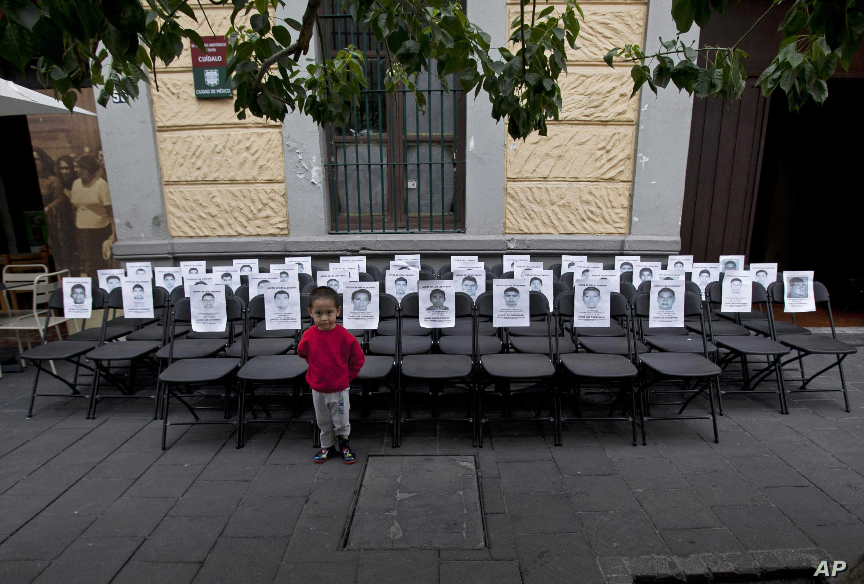 A child stands before a memorial made up of empty chairs bearing images of 43 missing students, set up to mark the nine-month anniversary of their disappearance, in Mexico City, June 27, 2015.