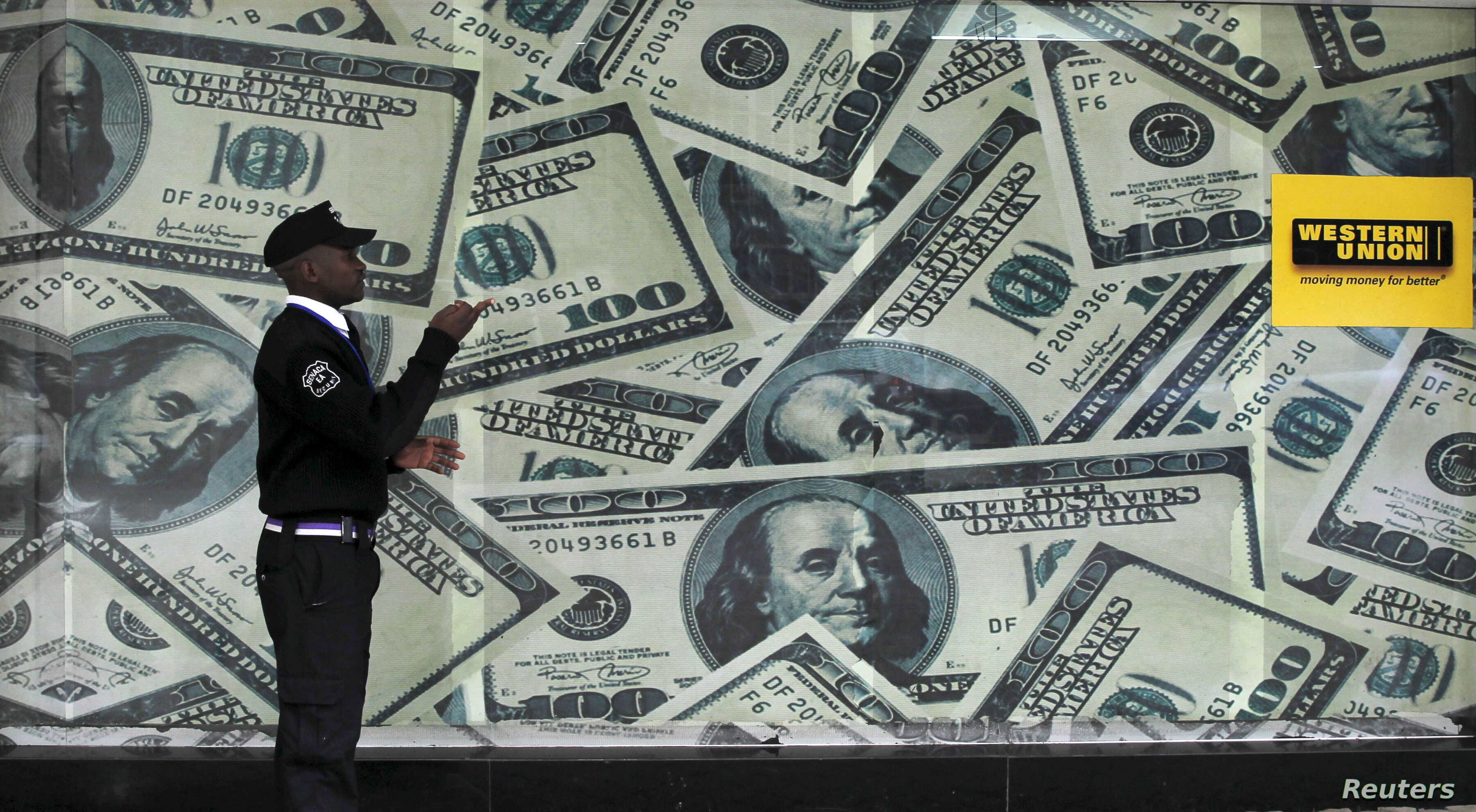 A security guard walks past a montage of old U.S. dollar bills outside a currency exchange bureau ahead of a scheduled State visit by the U.S. President Barack Obama in Kenya's capital Nairobi, July 23, 2015.