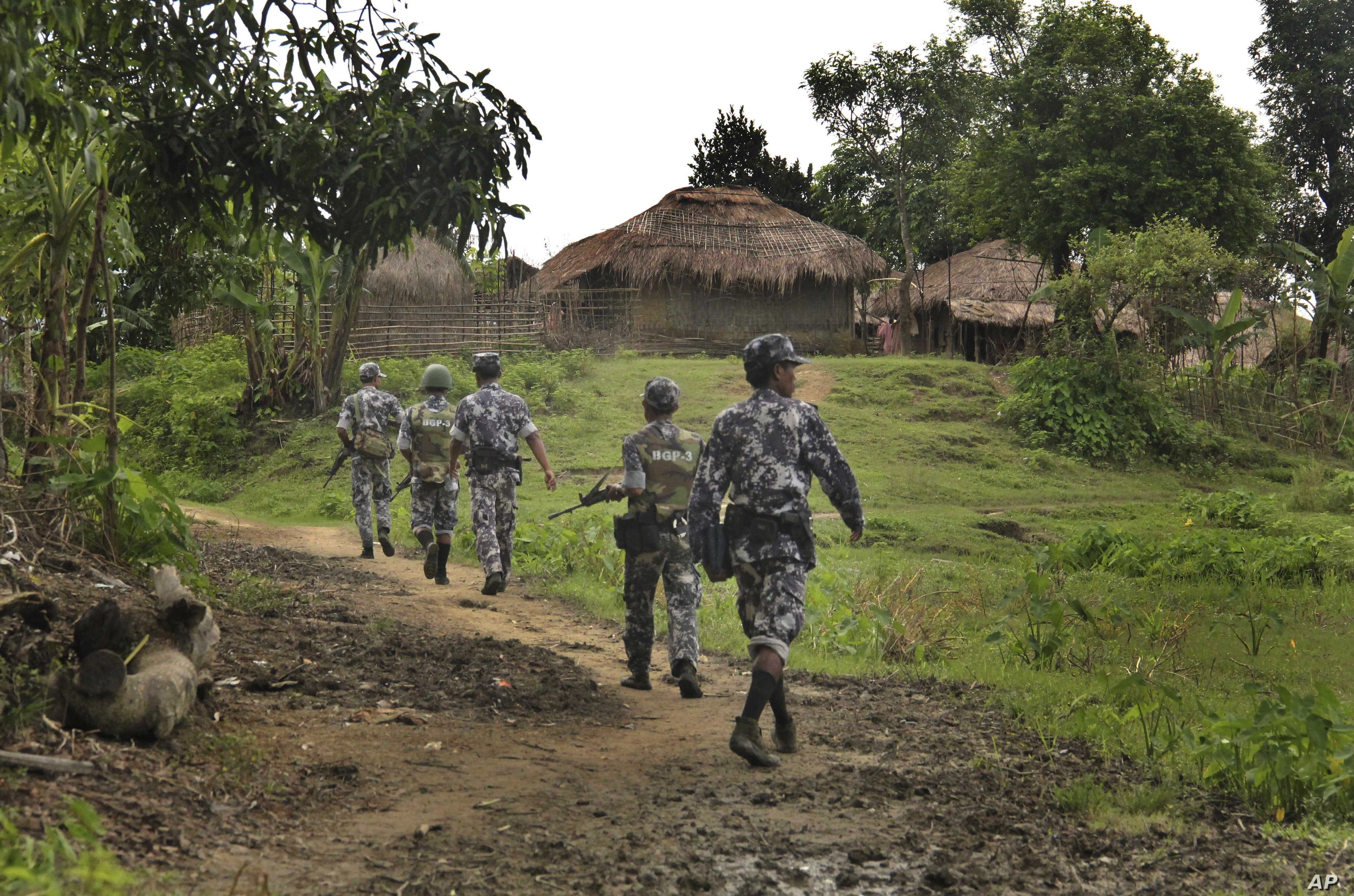 In this July 14, 2017 photo, Myanmar Border Guard Police (BGP) officers walk along a path in Tin May village, in which Myanmar government and military claim the existence of Muslim terrorists in Rakhine State, Myanmar.