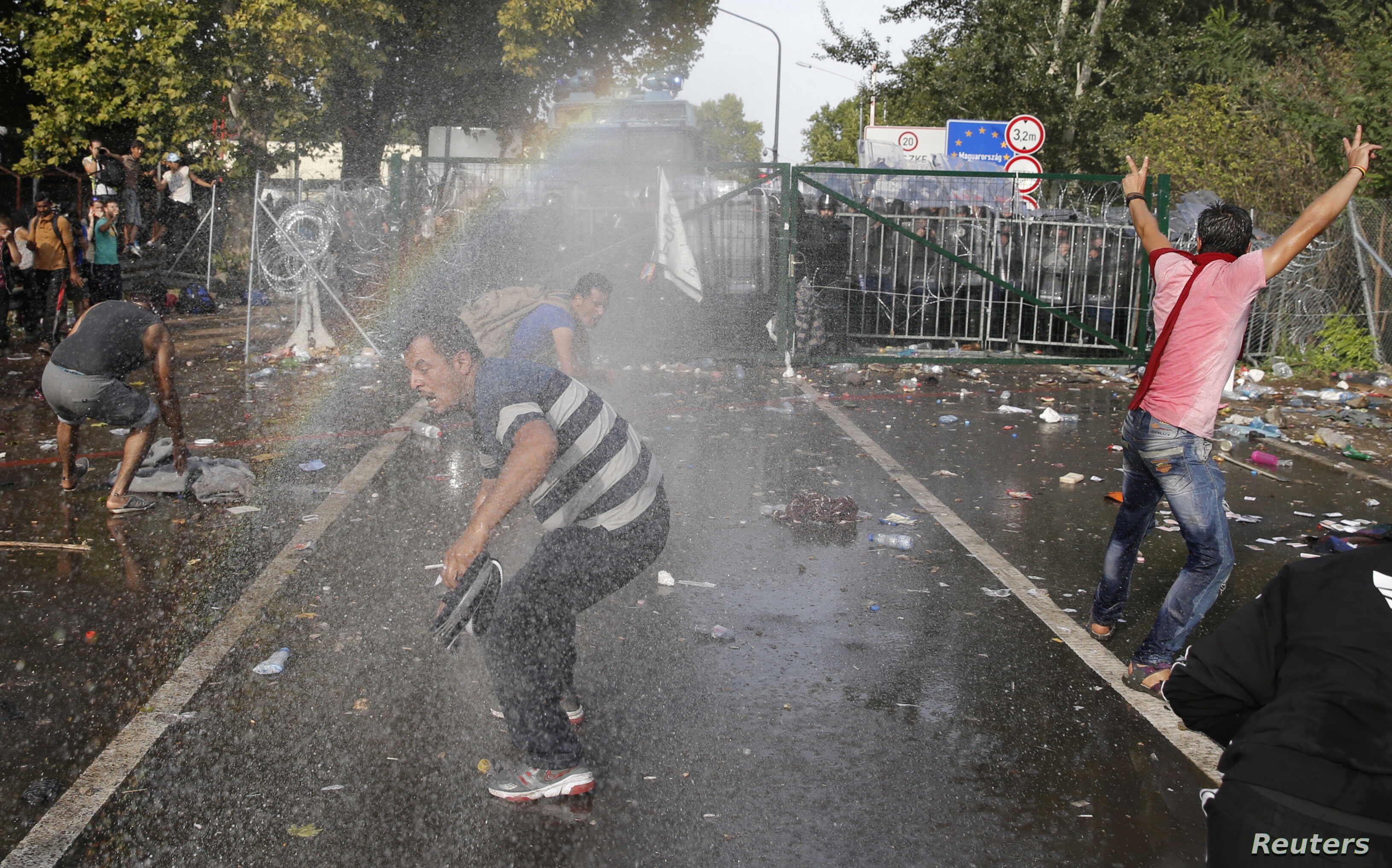 Migrants react on the Serbian side of the border as Hungarian riot police fires tear gas and water cannon near Roszke, Hungary, Sept.16, 2015.