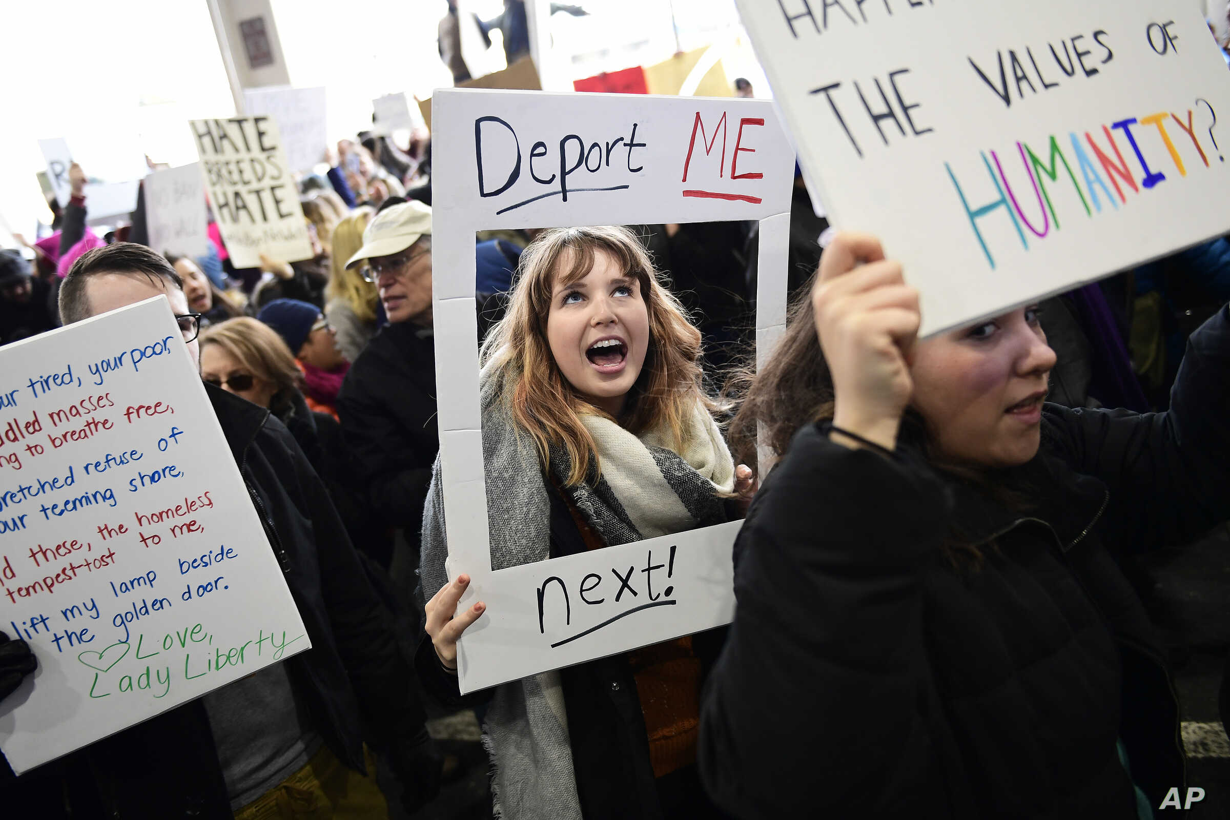 Madison Gray, a Temple University student, holds up her sign during a protest against President Donald Trump's executive order banning travel to the U.S. by citizens of Iraq, Syria, Iran, Sudan, Libya, Somalia or Yemen, Sunday, Jan. 29, 2017, at Phil...