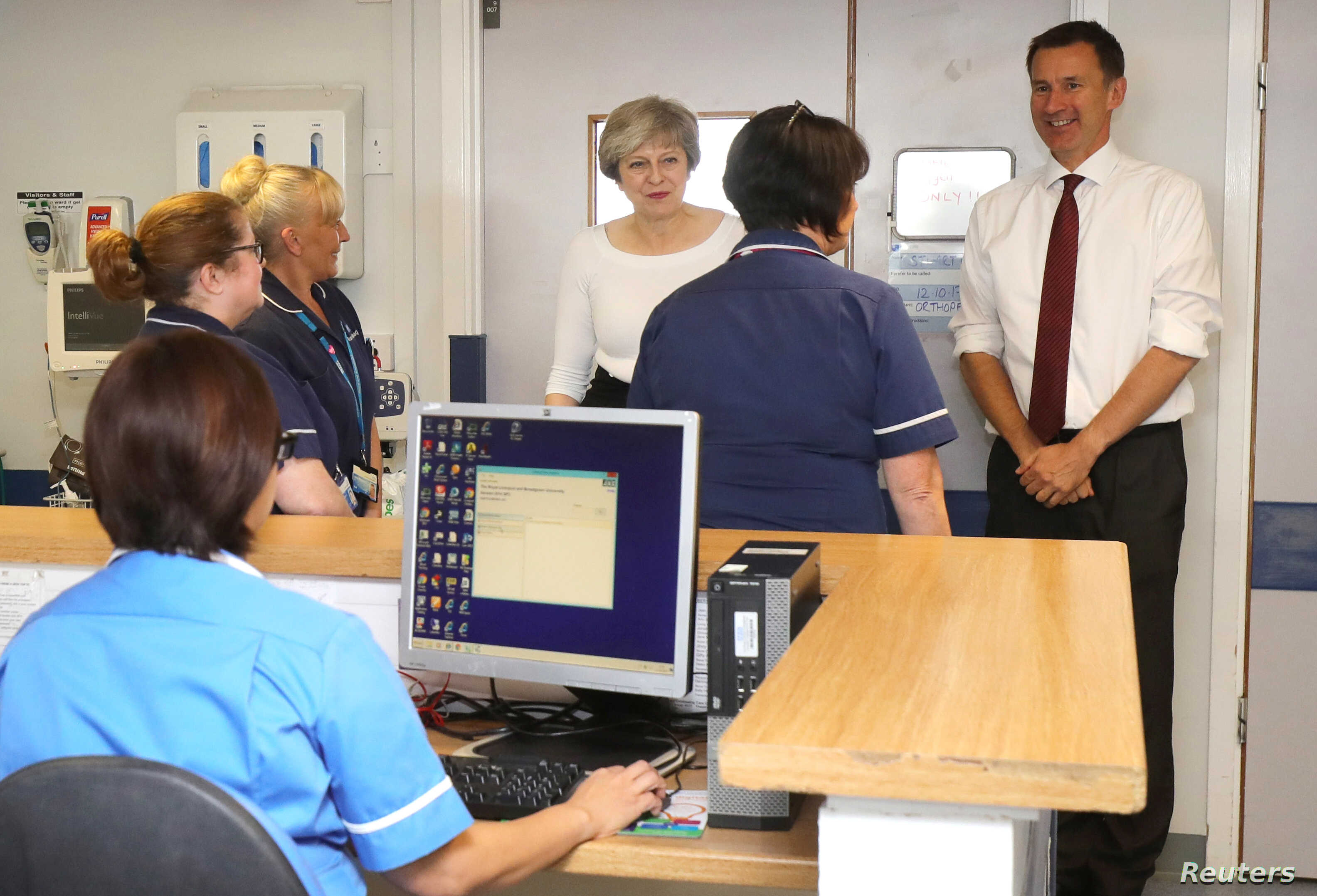 FILE - Britain's PM Theresa May and Secretary of State for Health Jeremy Hunt speak to nurses and members of staff as they visit the Renal Transplant Unit at the Royal Liverpool University Hospital, Liverpool, Oct. 12, 2017.