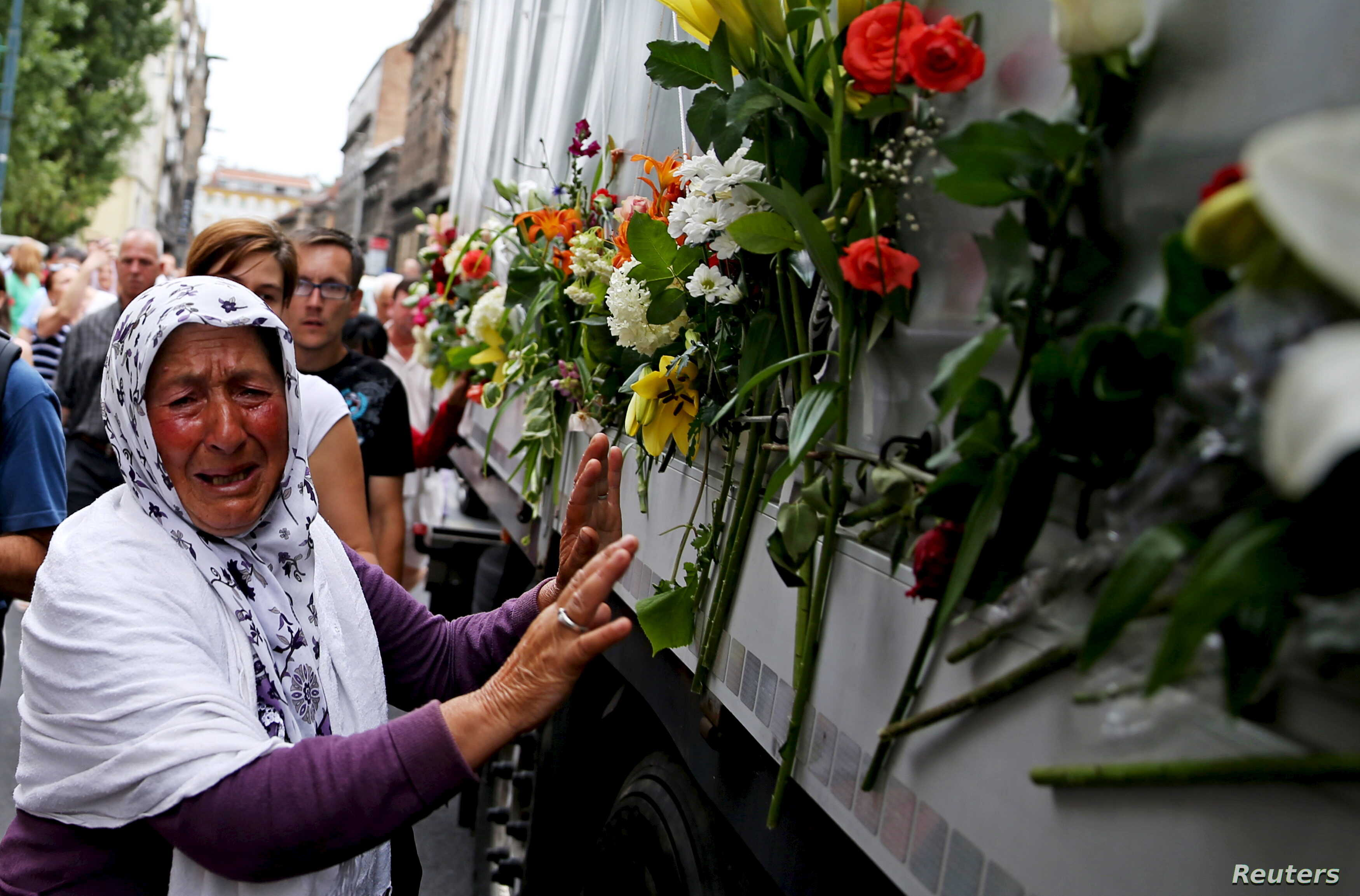 A woman cries beside a truck carrying 136 coffins of newly identified victims of the 1995 Srebrenica massacre, in front of the presidential building in Sarajevo July 9, 2015. The bodies of the 136 recently identified victims of Srebrenica massacre wi...