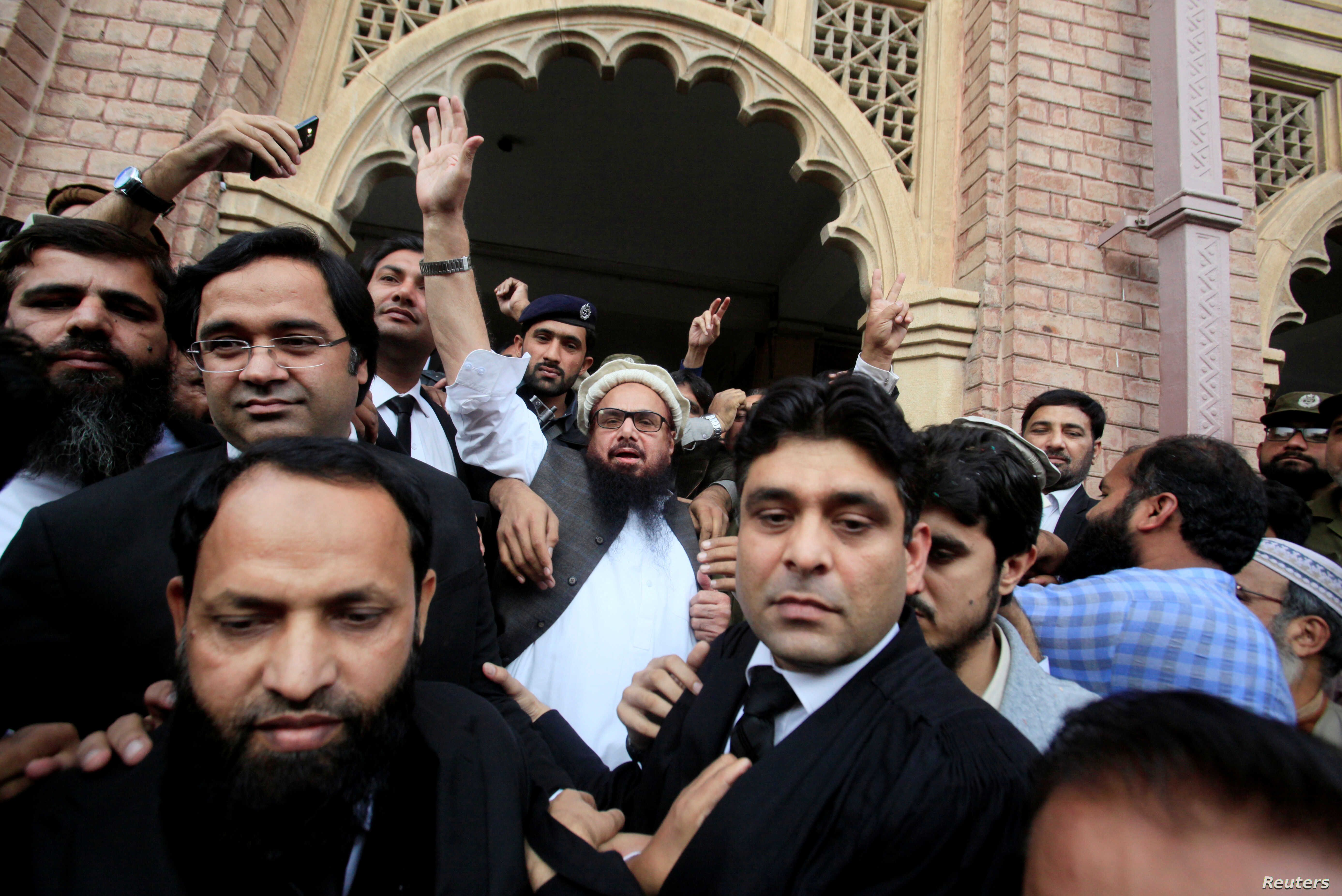 Hafiz Saeed (C) reacts to supporters as he walks out of court after a Pakistani court ordered his release from house arrest in Lahore, Pakistan, Nov.  22, 2017.