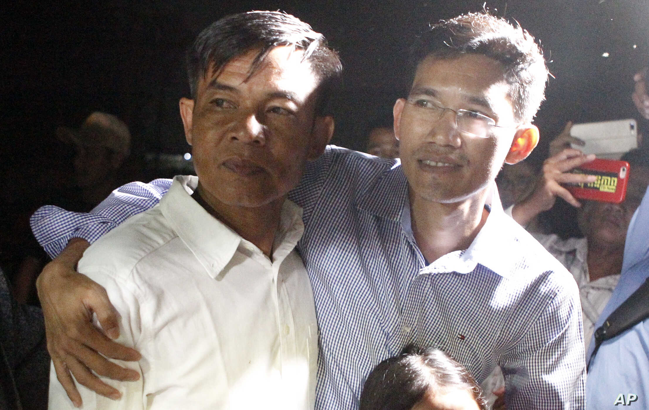 Two former Radio Free Asia reporters Uon Chhin, left, and Yeang Socheamet, right, hold together after they walk outside the main prison of Prey Sar at the outskirt of Phnom Penh, Cambodia, Aug. 21, 2018.