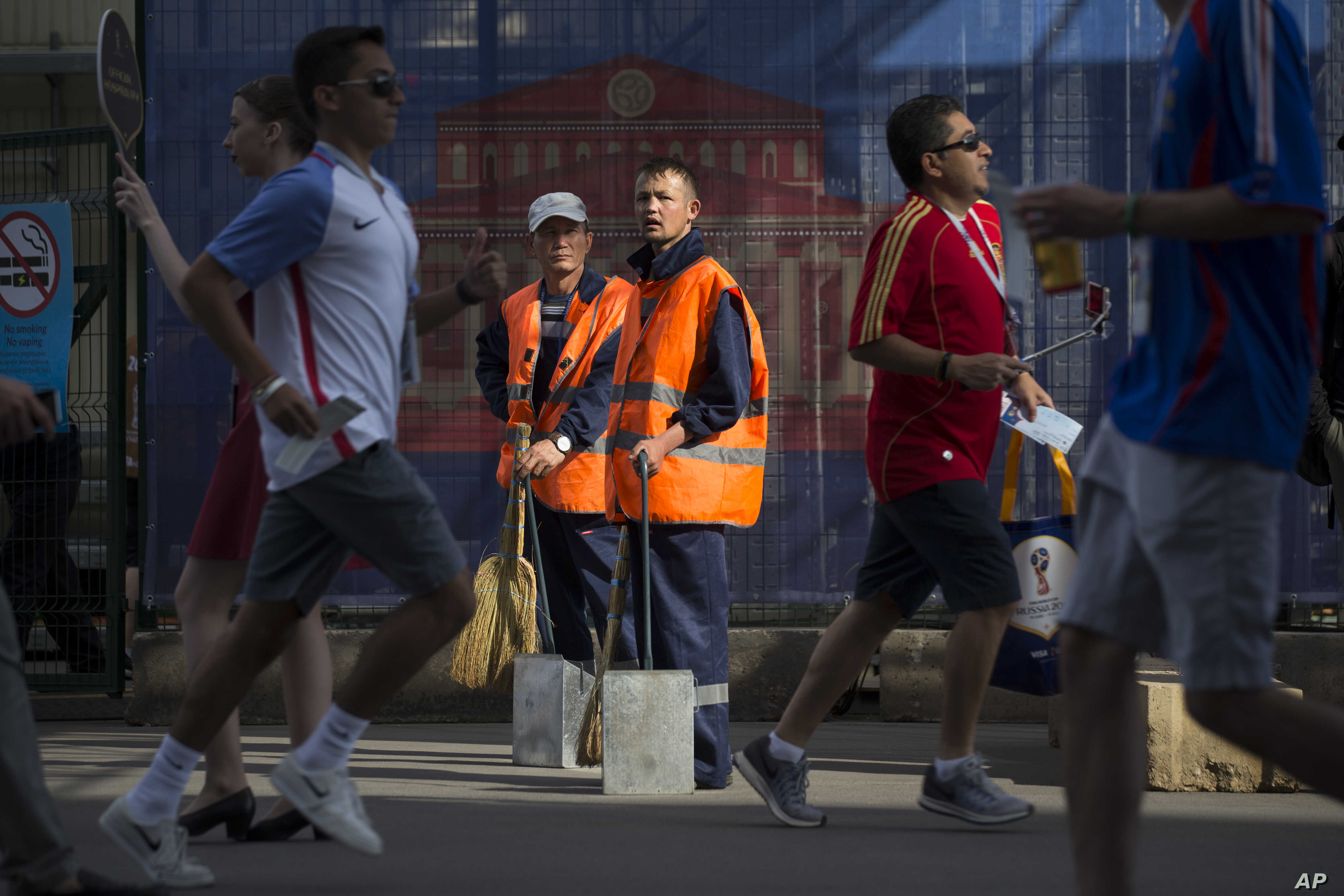 FILE - Two migrant municipal workers stand ready to clean at Moscow's Luzhniki Stadium in Moscow, Russia, June 26, 2018.