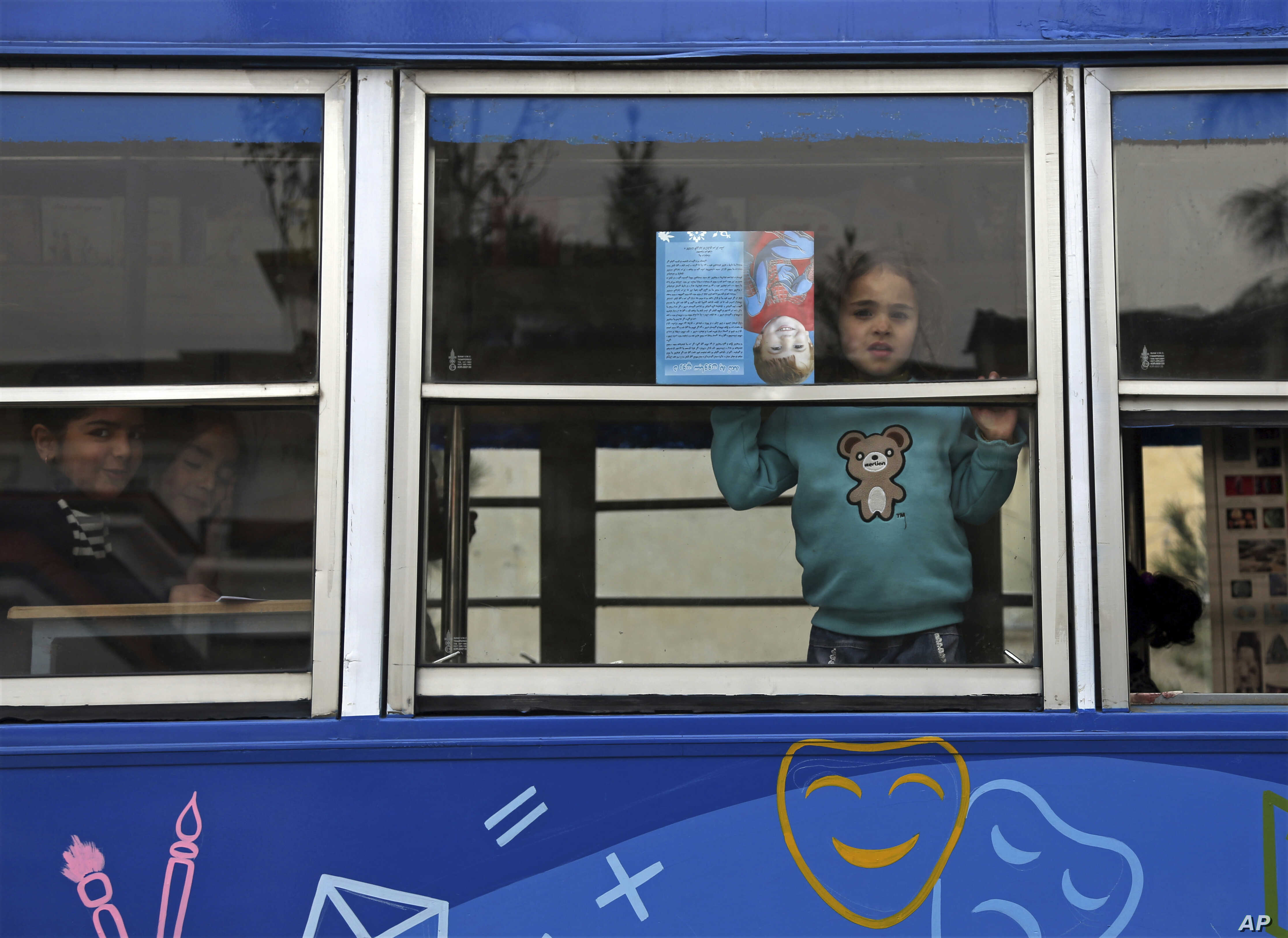 Children look out the window of a library on wheels, in Kabul, Afghanistan, March 10, 2018.