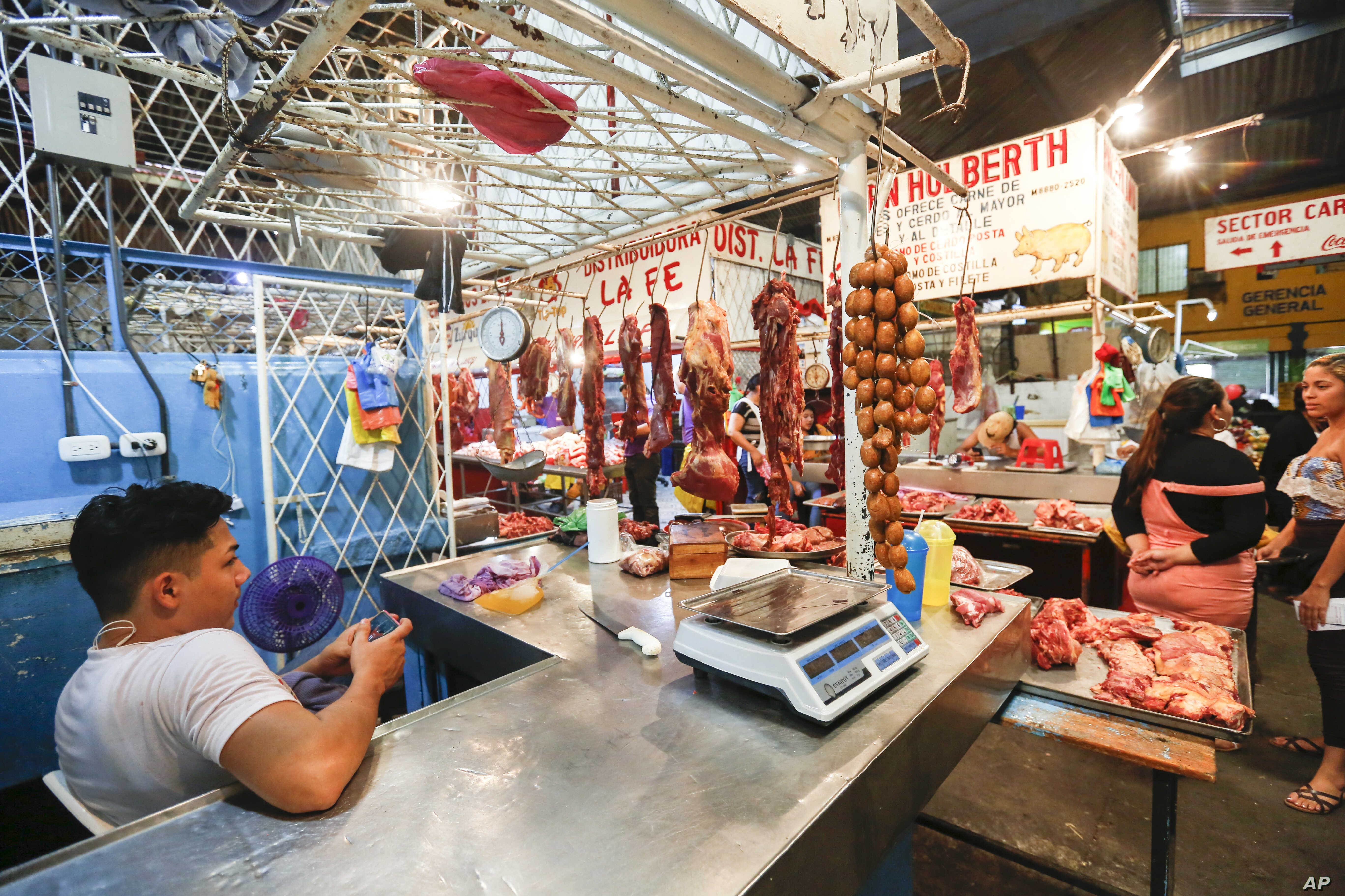 A vendor waits for customers at a market in Managua, Nicaragua, Dec. 21, 2018. In the streets of Managua, outward appearances suggest some degree of normality. But vendors say business has been running 25 to 30 percent below what it was last year, ev...