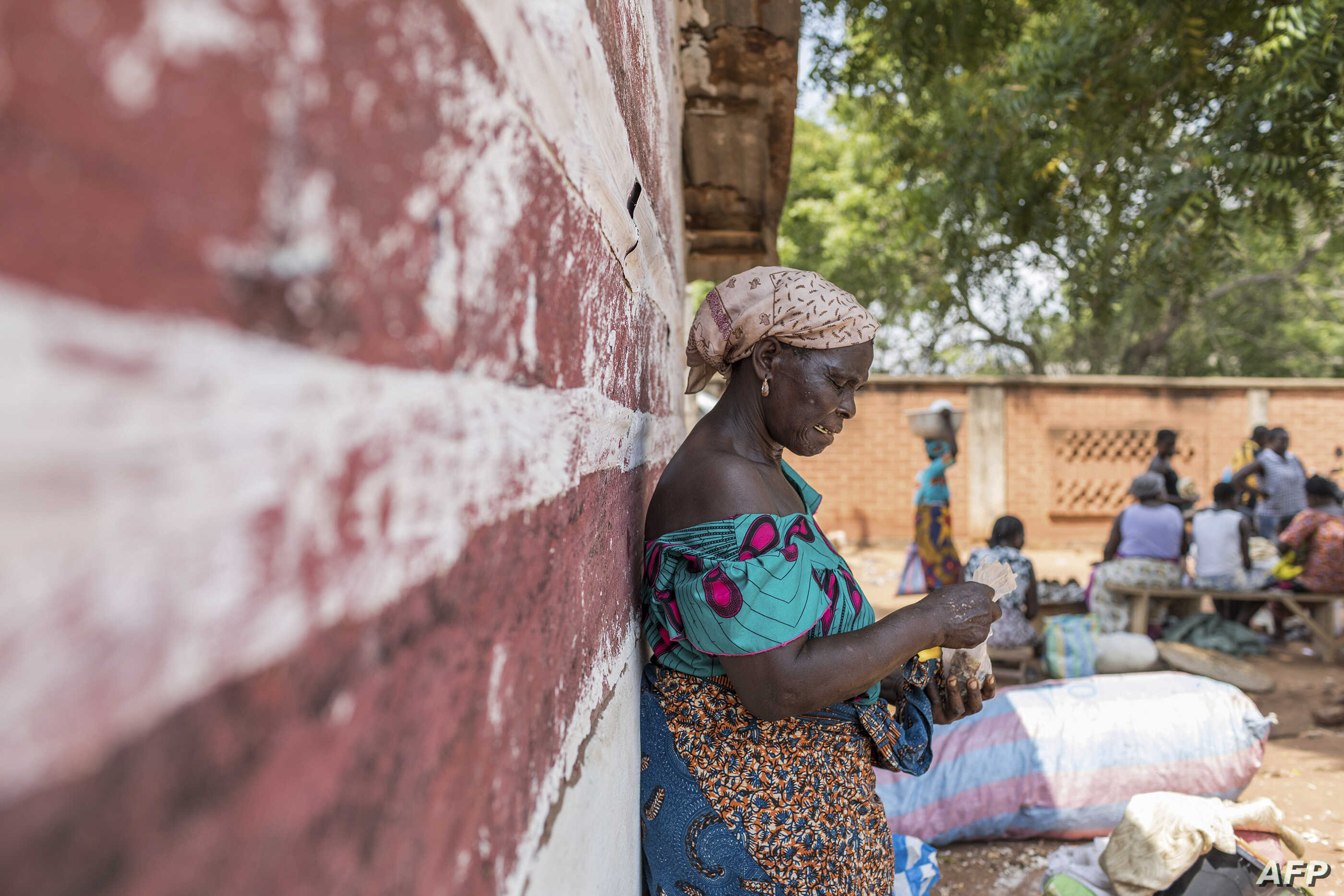 FILE - A vendor waits for customers to exchange her goods for other goods at the barter market in Togoville, Nov. 24, 2018.