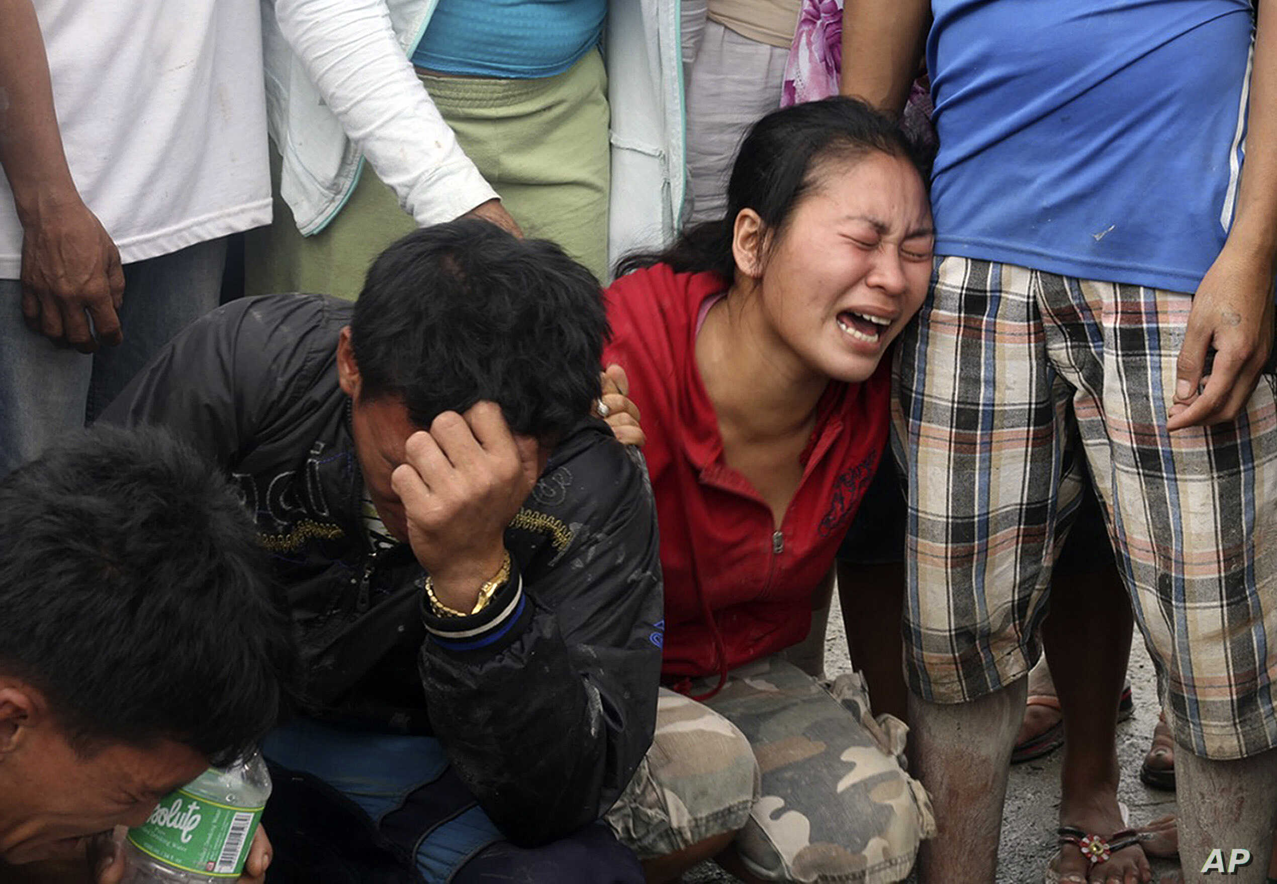 Relatives grieve as they view bodies recovered from floods in New Bataan, Compostela Valley province, southern Philippines Dec. 5, 2012.