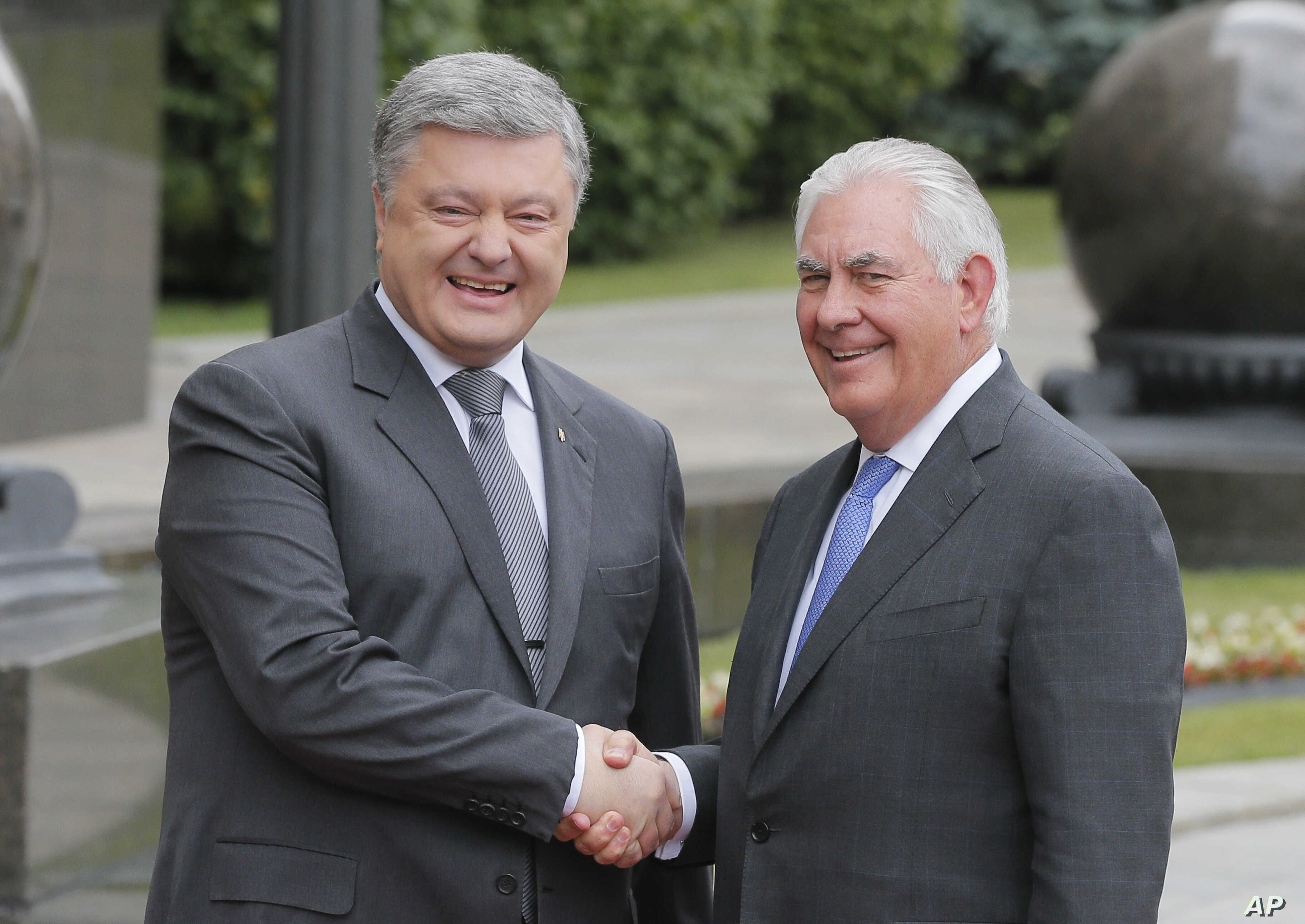 Ukrainian President Petro Poroshenko, left, and U.S. Secretary of State Rex Tillerson shakes hands before a meeting in Kyiv, Sunday, July 9, 2017.