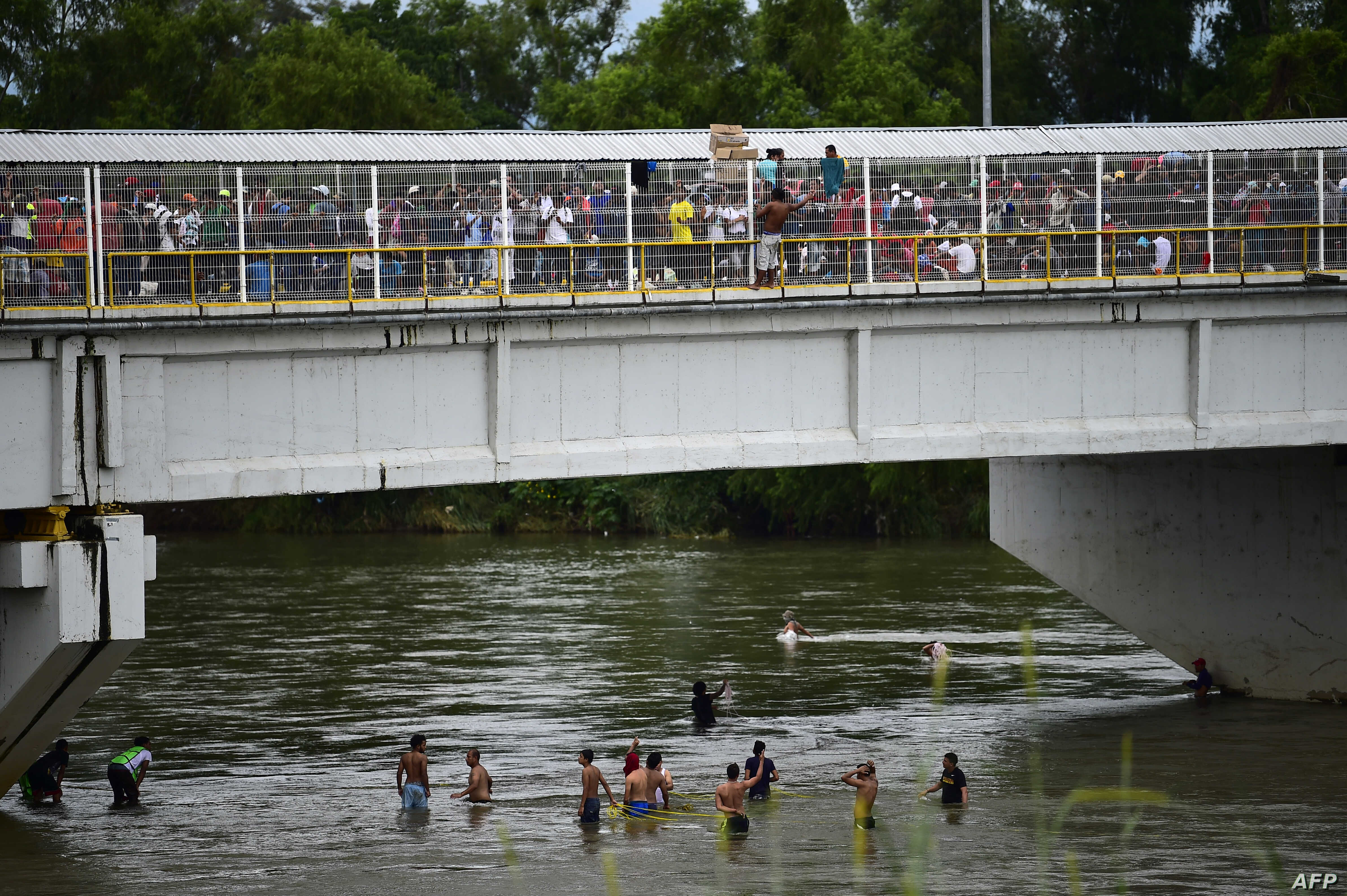 Honduran migrants heading in a caravan to the US, wait to help fellow men get down to the Suchiate River from the Guatemala-Mexico international border bridge, in Ciudad Hidalgo, Chiapas state, Mexico, Oct. 20, 2018.