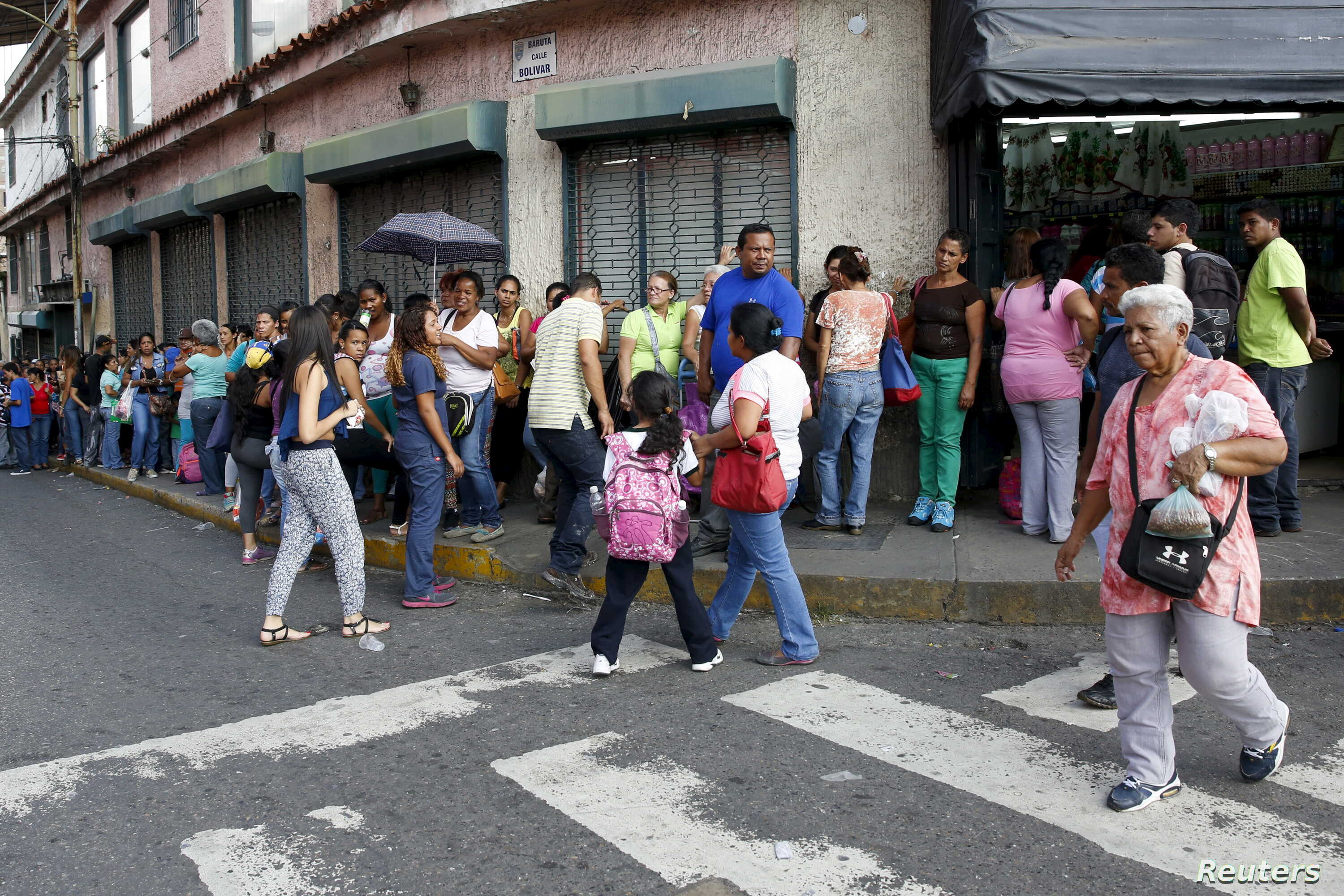 People wait in a line to buy staple goods outside a supermarket in Caracas, Venezuela, Oct. 20, 2015.