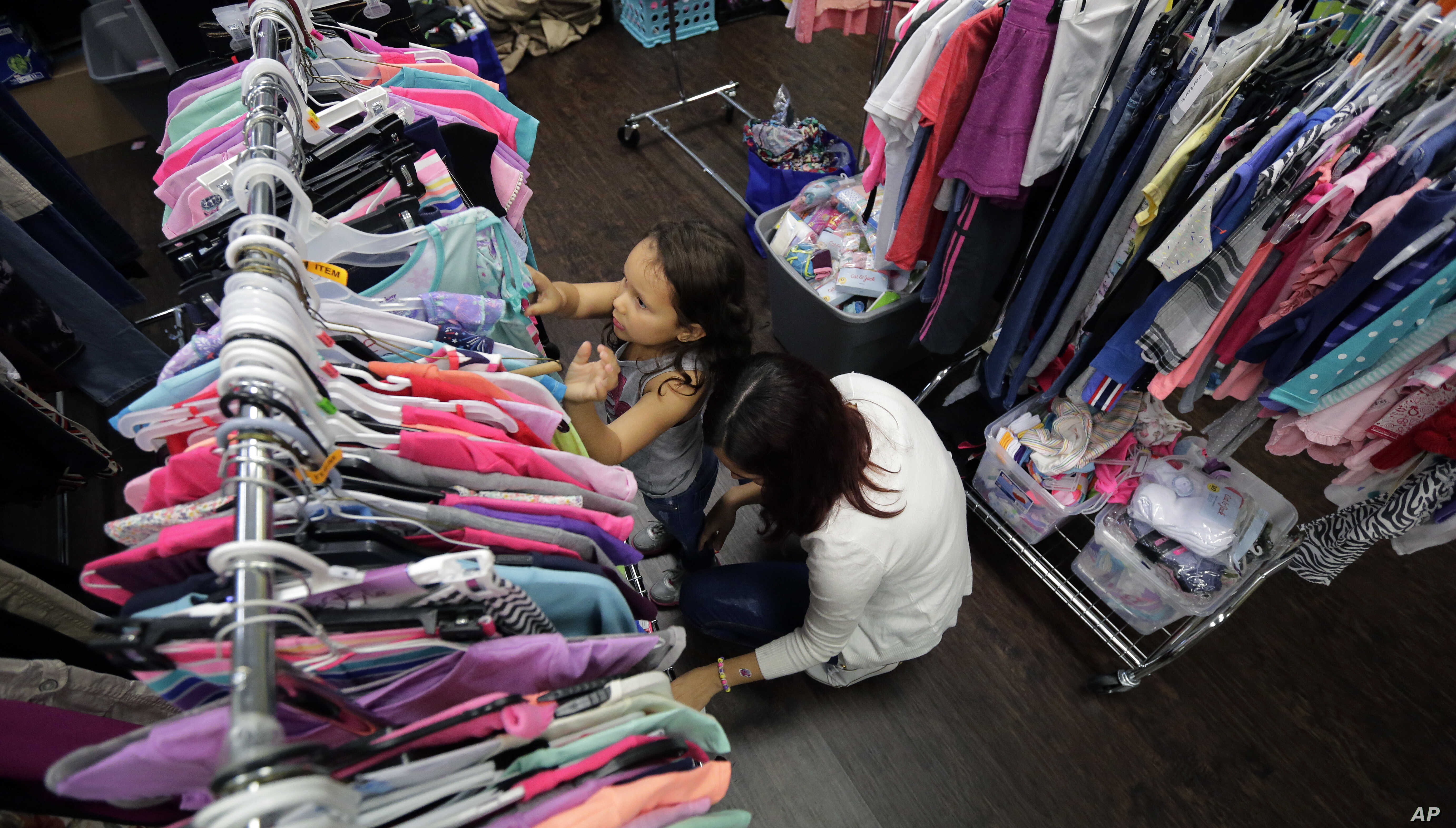 Immigrants seeking asylum, Natalia Oliveira da Silva and her daughter, Sara, 5, look through donated clothing at a Catholic Charities facility, July 23, 2018, in San Antonio, Texas.