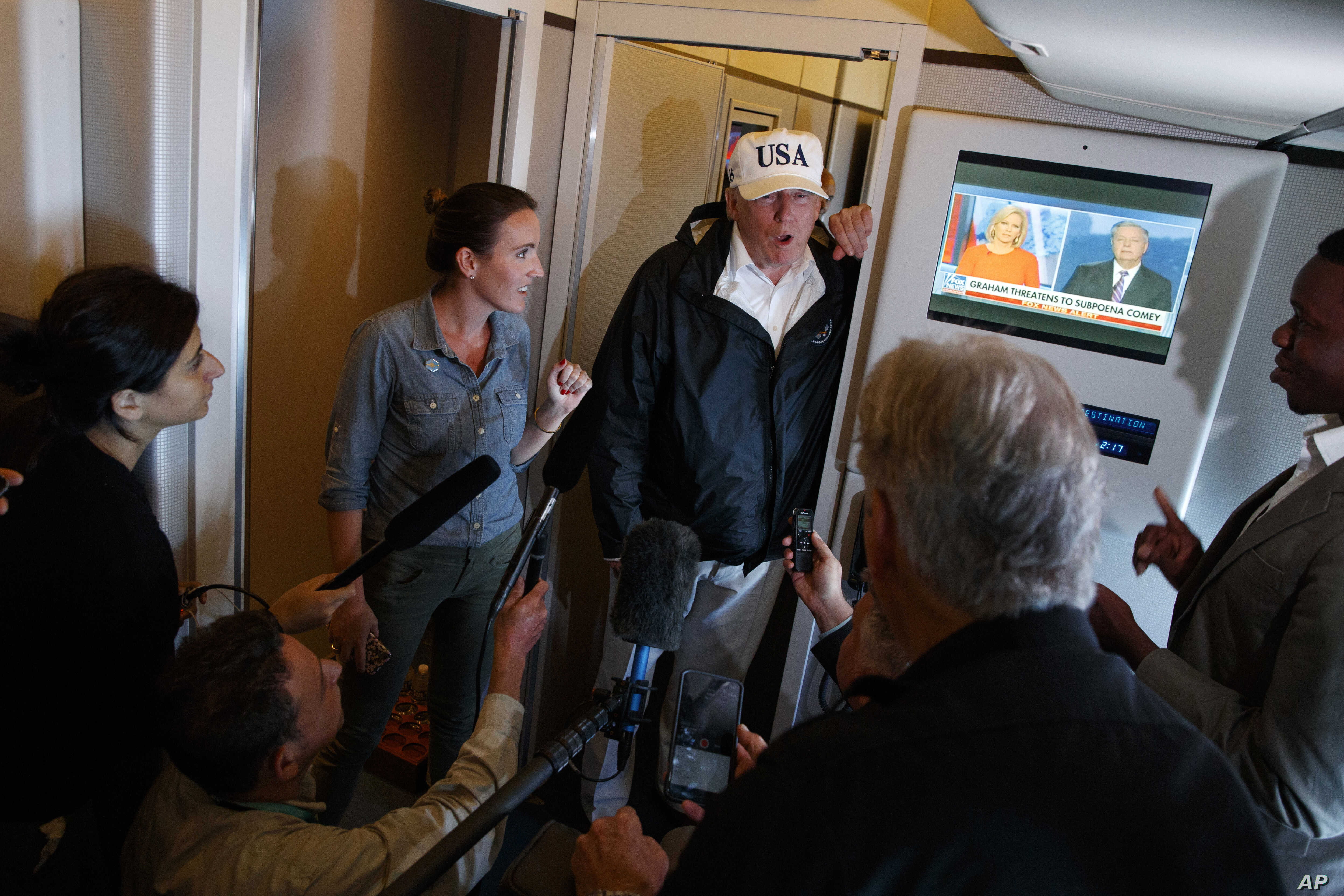 President Donald Trump talks with reporters aboard Air Force One, en route to Washington, Sept. 14, 2017.