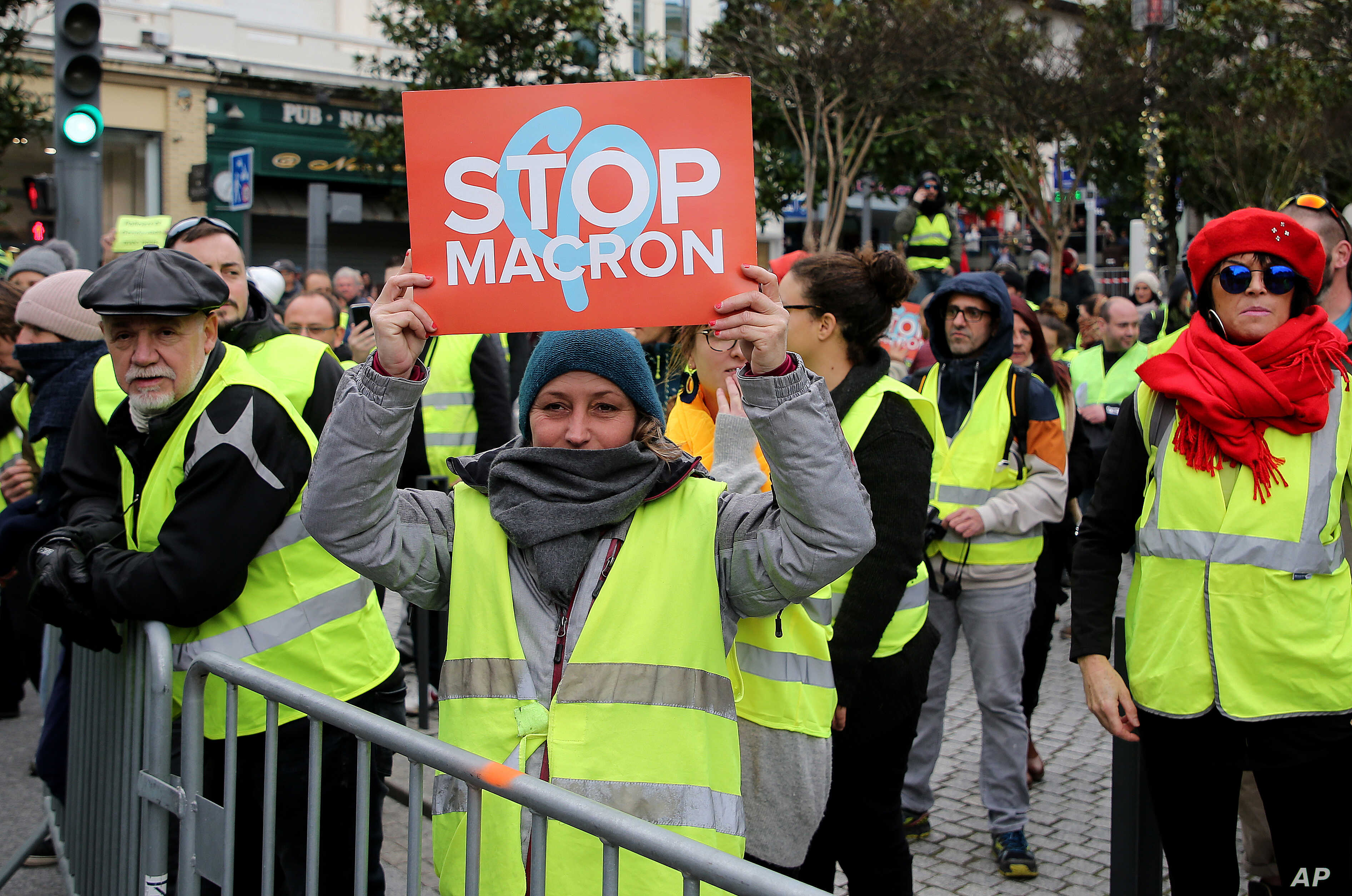 A demonstrator wearing her yellow vest holds a placard during a visit by French Foreign Minister Jean-Yves Le Drian in Biarritz, southwestern France, Dec. 18, 2018.