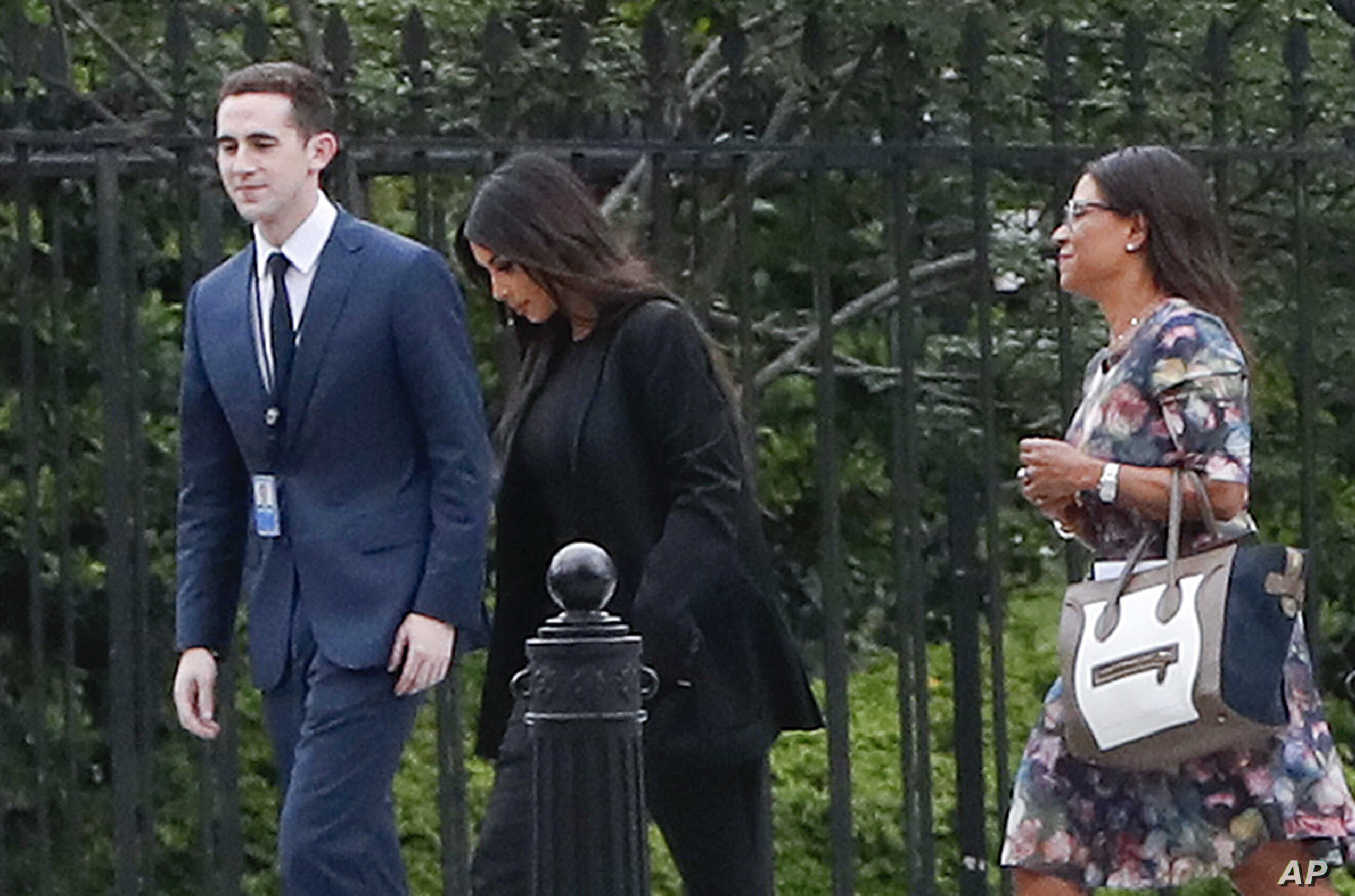 FILE - Kim Kardashian, center, arrives with her attorney Shawn Chapman Holley at the security entrance of the White House in Washington, May 30, 2018.
